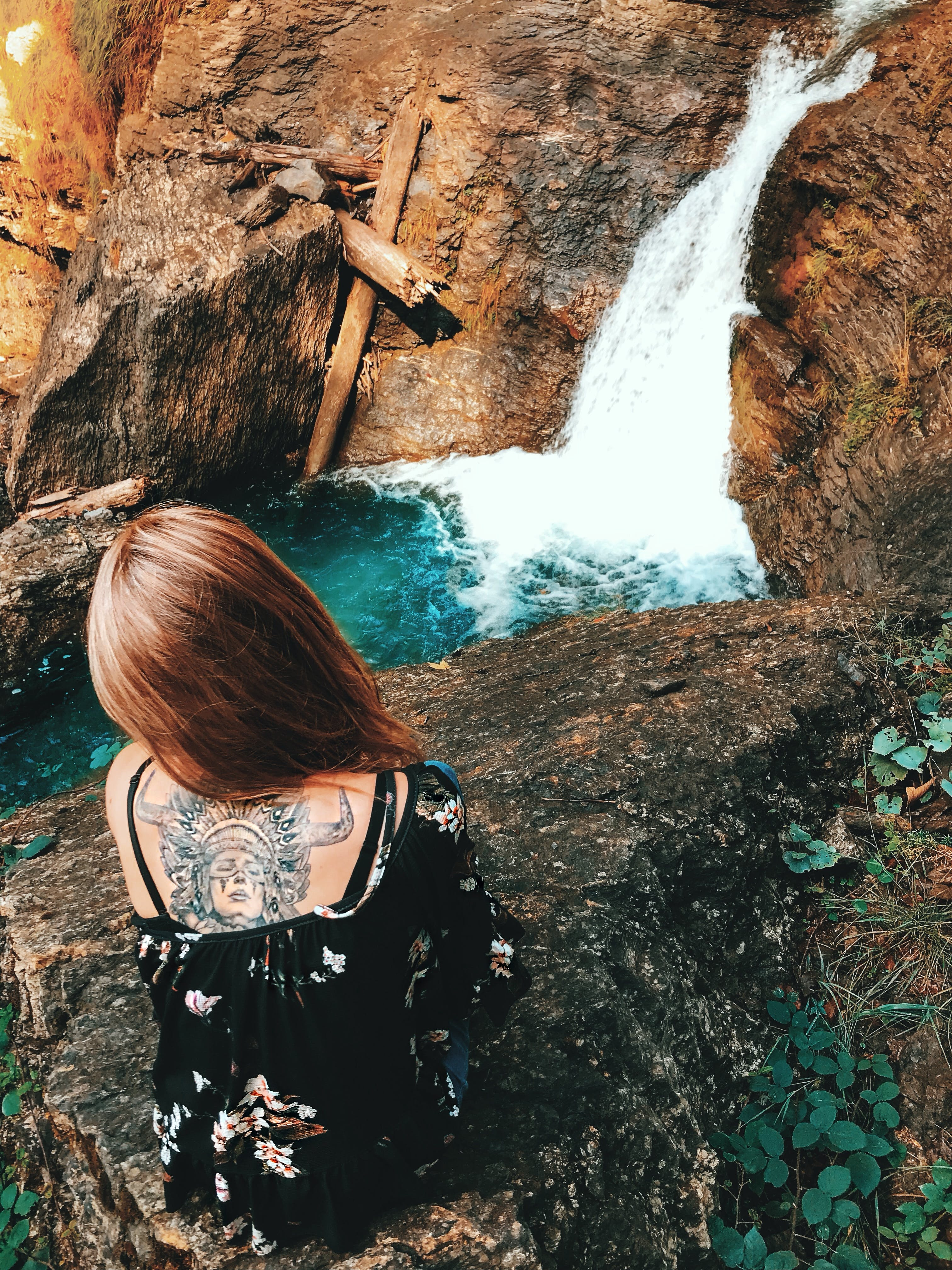 Woman Sitting on Rock on Top of Waterfalls