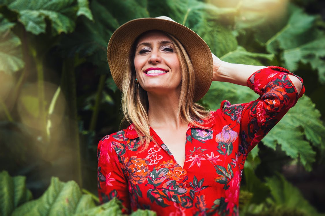 Woman Holding Her Back Head Wearing Brown Hat and Red and Multicolored Floral Button-up Long-sleeved Blouse