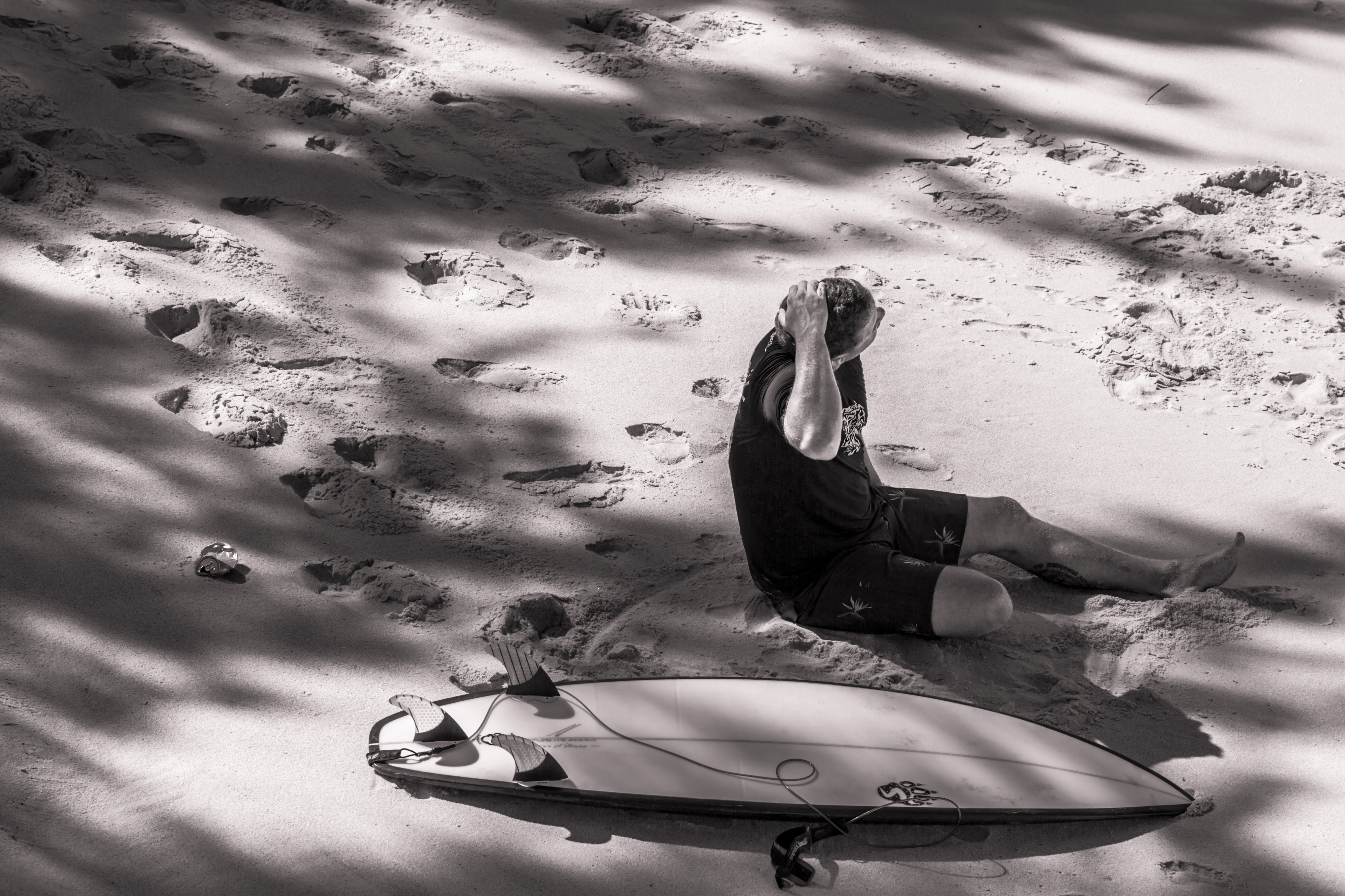 Grayscale Photo of Man Sits Beside Surfboard on Sand