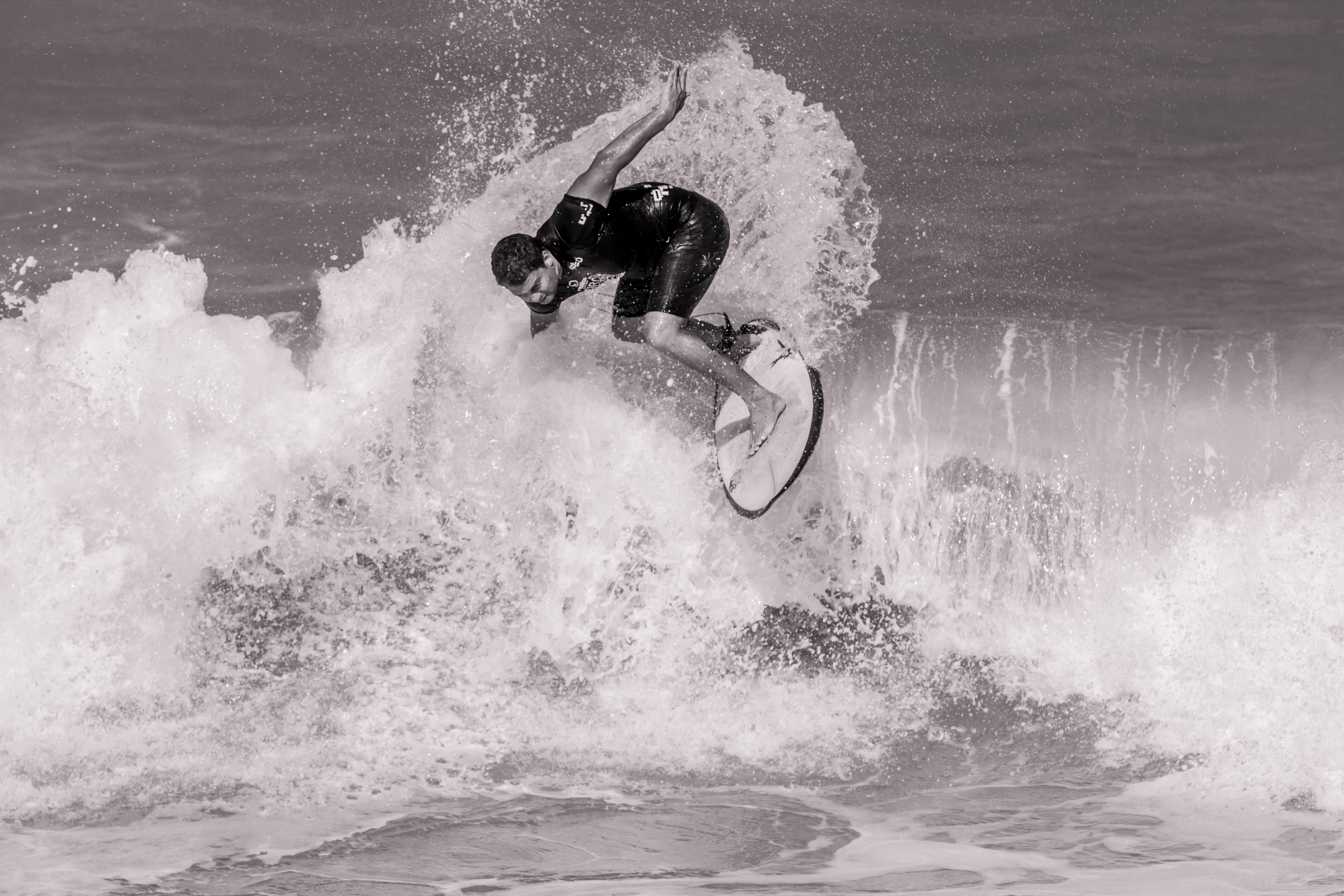 Grayscale Photo of Surfer on Ocean Waves