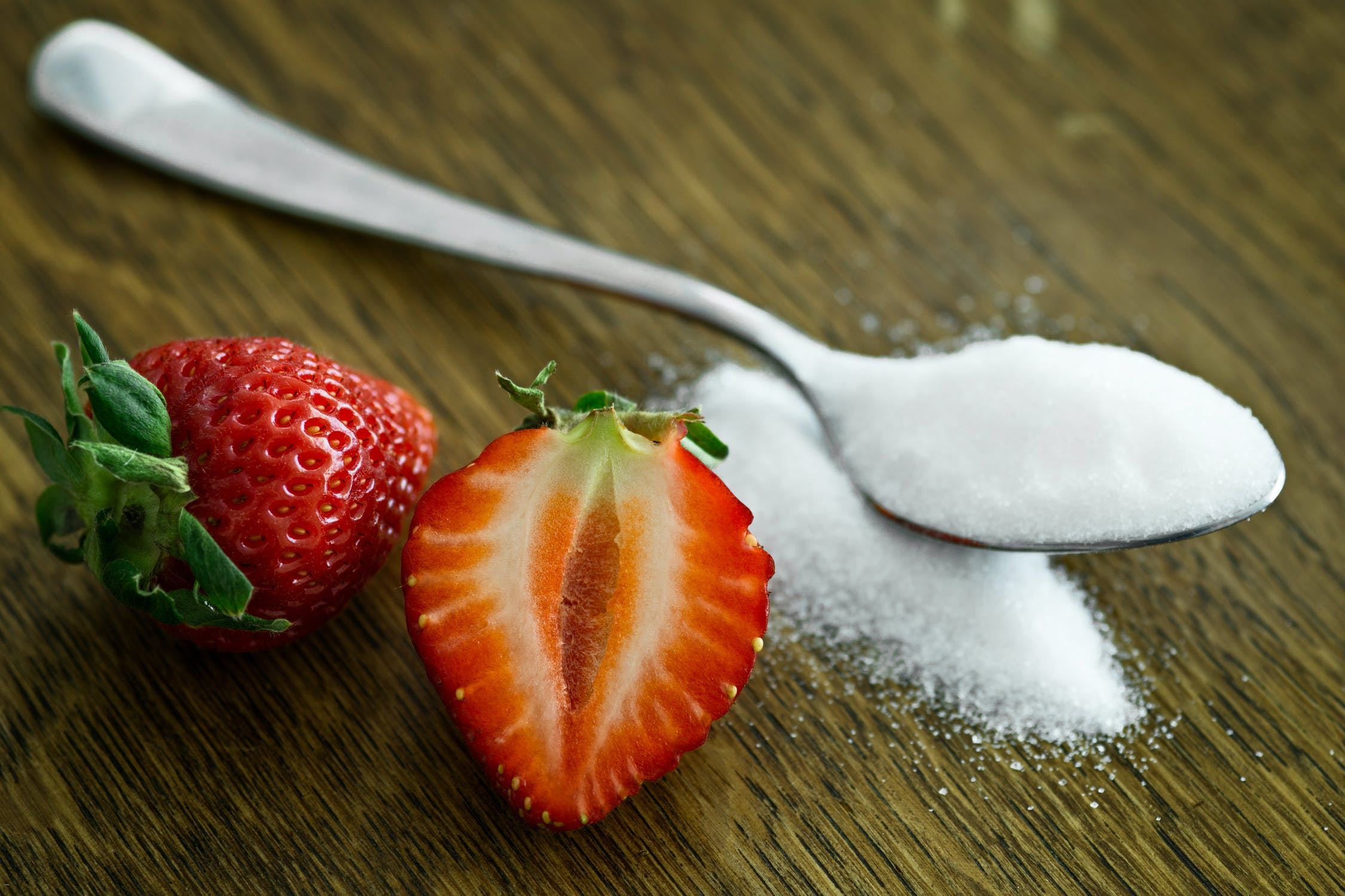 sugar in a spoon next to a cut up strawberry