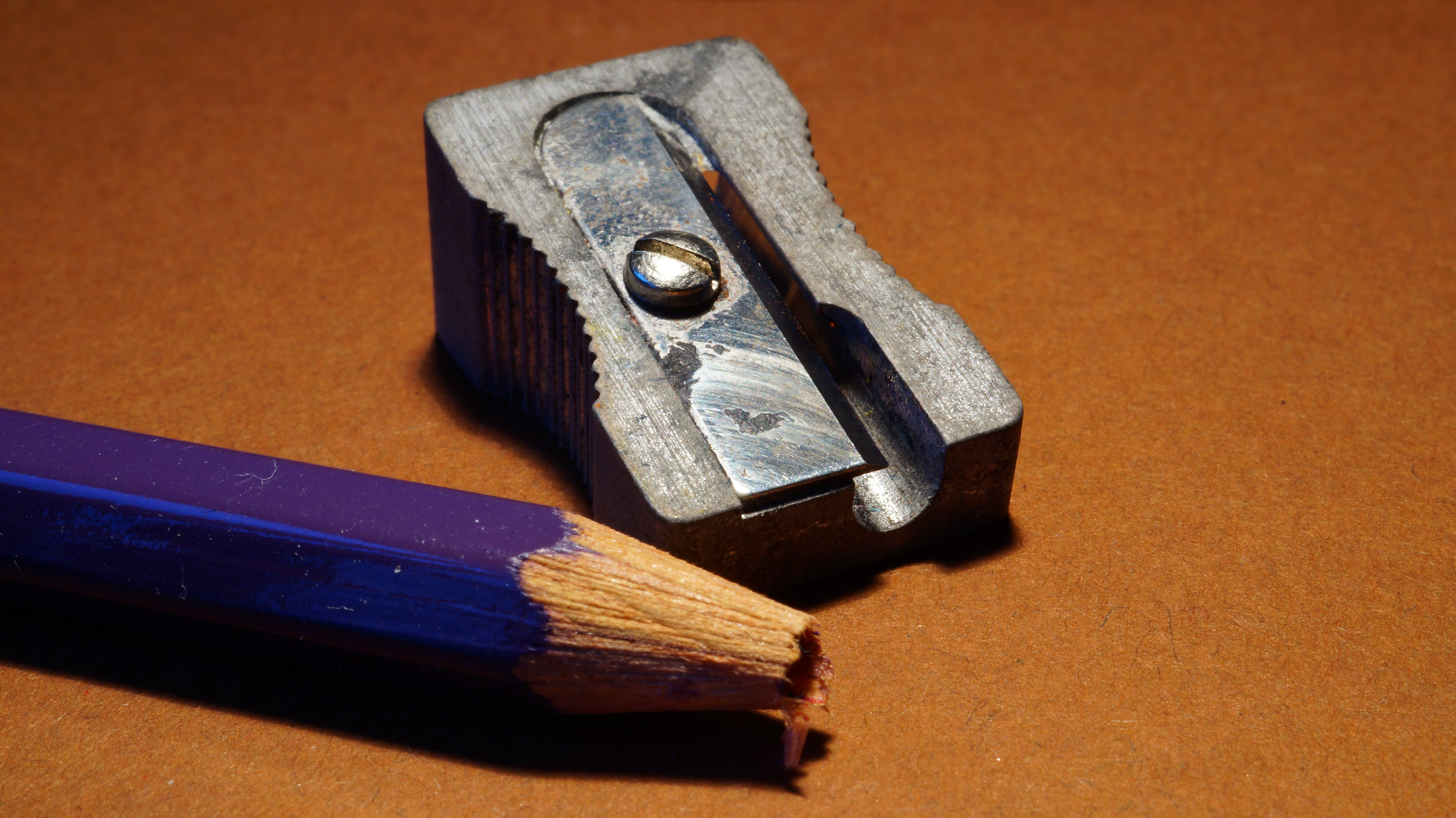Blue Pencil Beside Gray Sharpener on Brown Surface