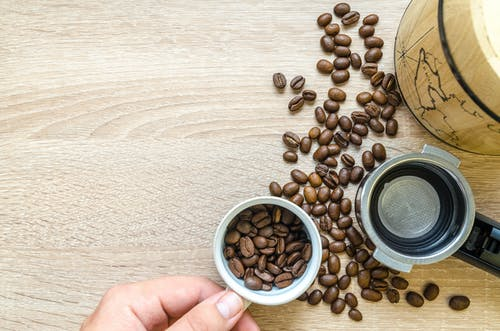 Person Holding Coffee Cup With Coffee Beans Near Coffee Press