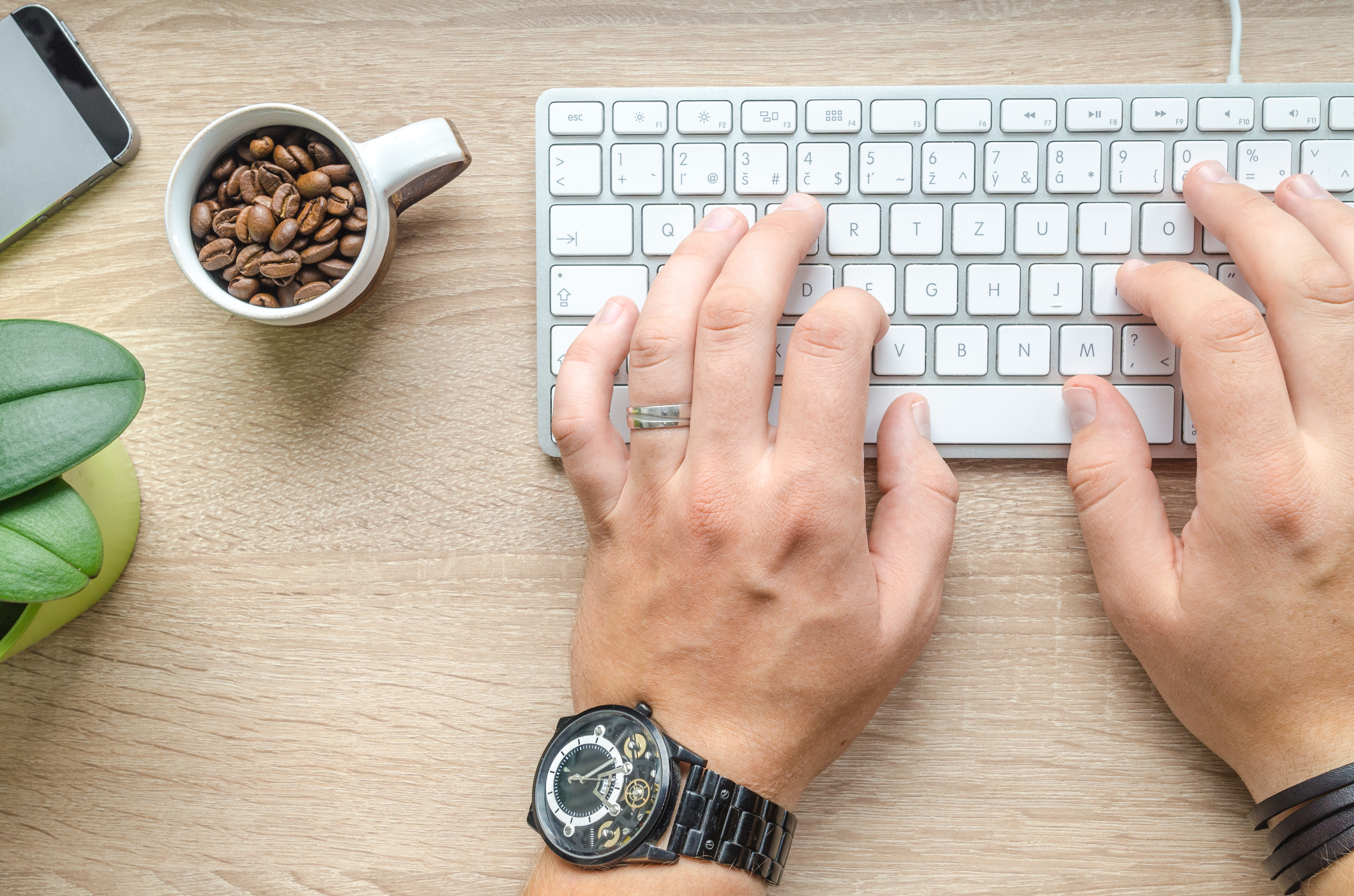 Person Using Silver Apple Magic Keyboard Beside of White Ceramic Mug With Coffee Beans