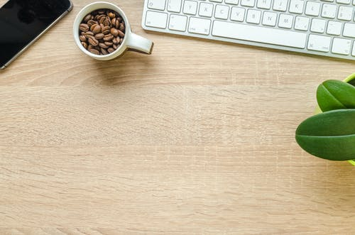 Coffee Beans in White Ceramic on Brown Wooden Table