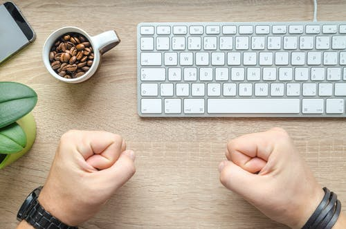 Person Near Apple Keyboard and Cup With Coffee Beans