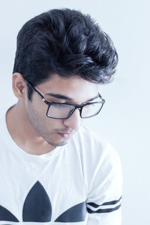 Man Wearing Black Framed Eyeglasses and White and Black Adidas Shirt