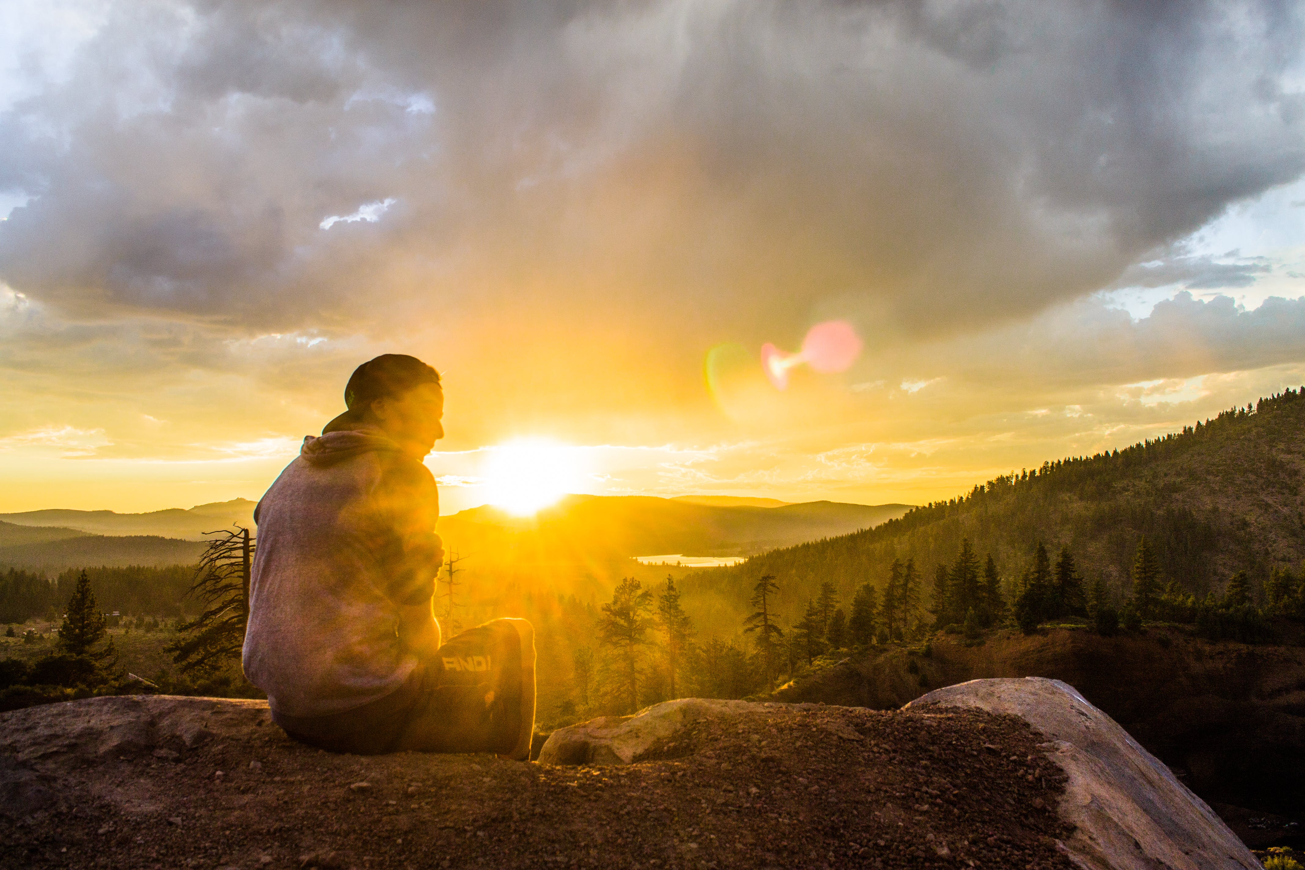 Person Sitting on Stone Facing Sunset