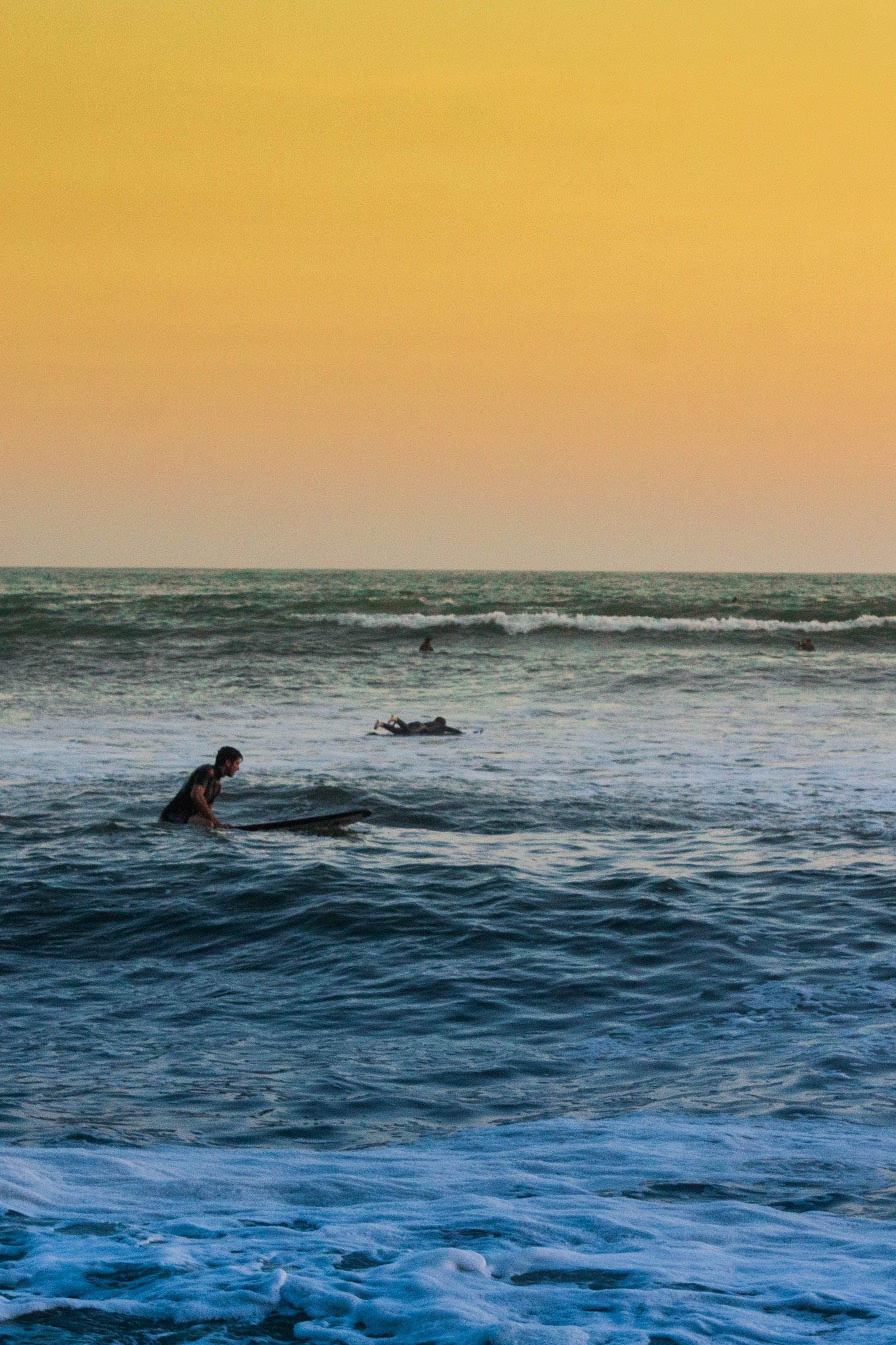Man Swimming on Sea Under Yellow Sky
