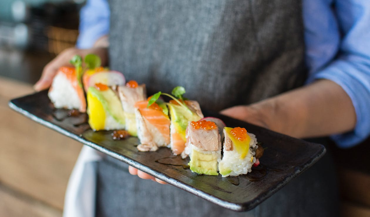 Person Holding Sushi on Black Plate