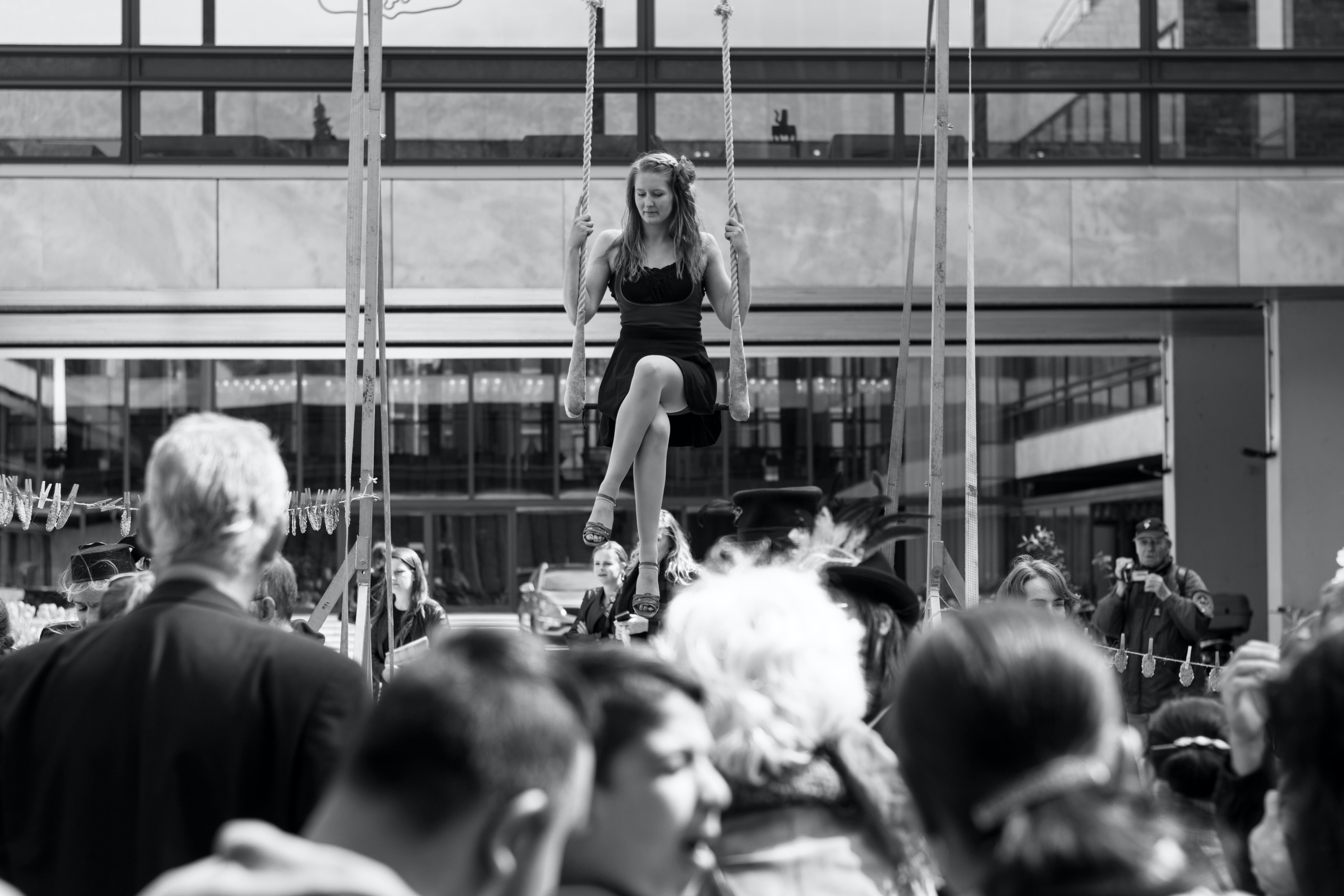 Greyscale Photography of a Crowd around Woman on Swing