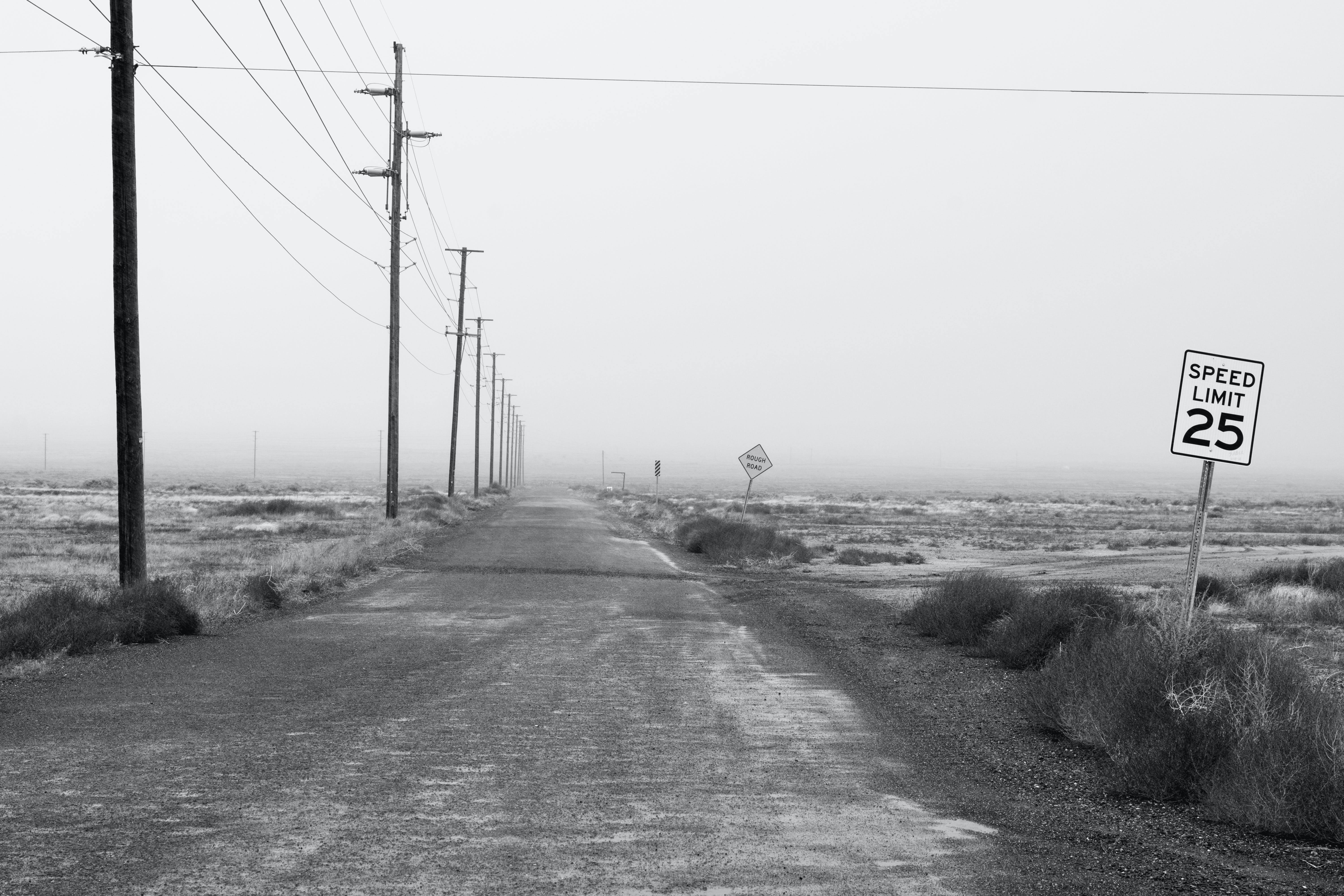 Monochrome Photography of an Empty Road With Speed Limit Sign