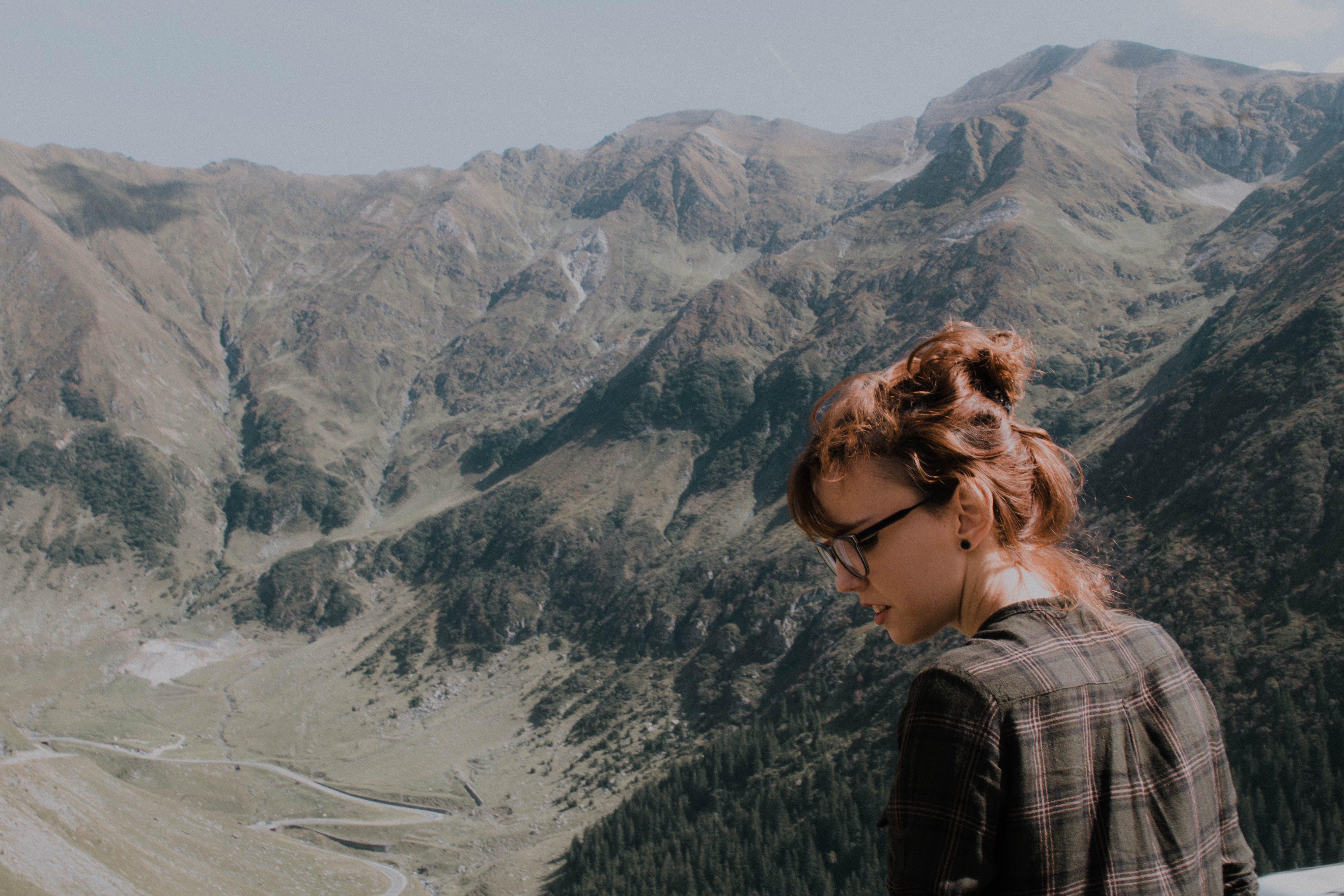 Woman Wearing Black Frame Eyeglasses Facing Green Mountains