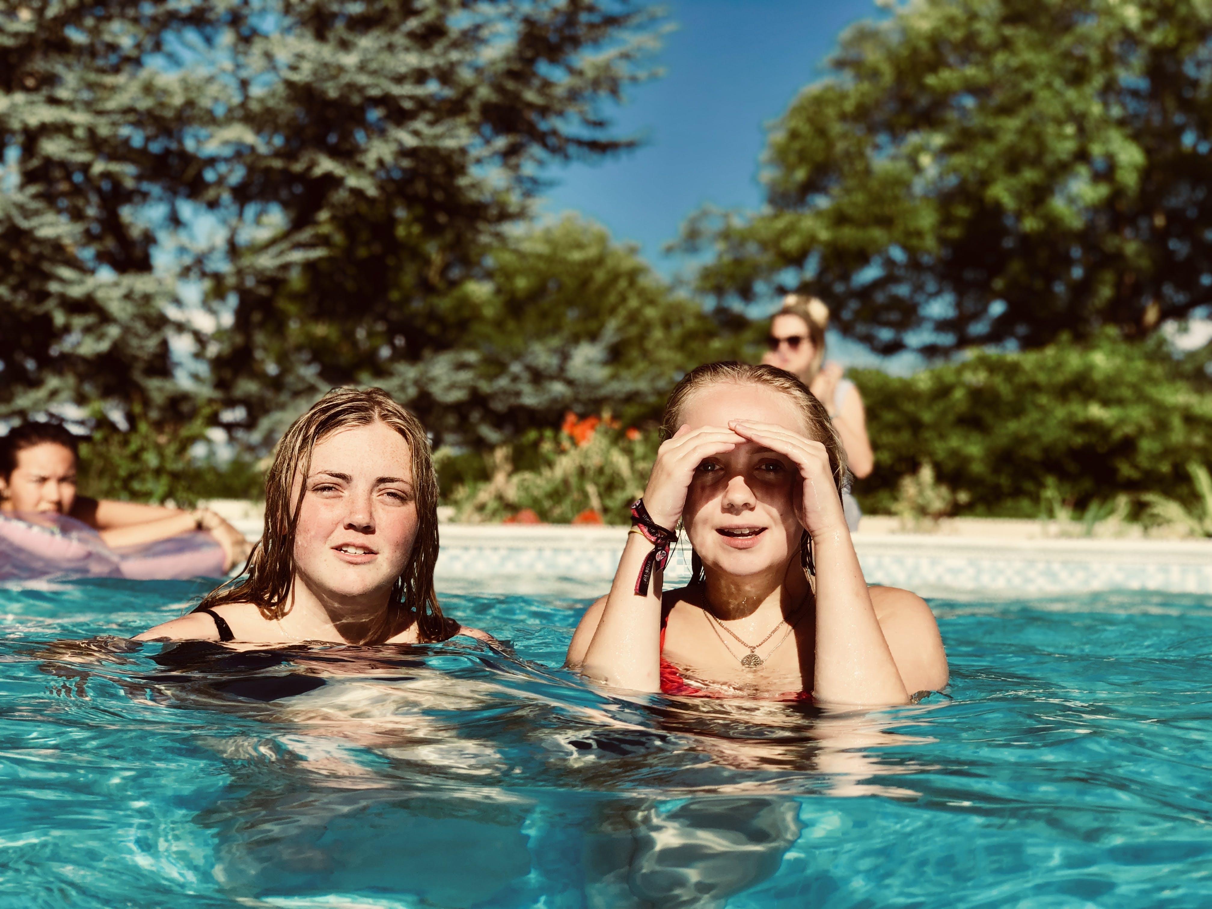 Two Women in Swimming Pool Near Trees
