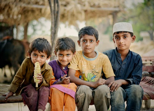 Four Children Sitting on Brown Charpai Bed