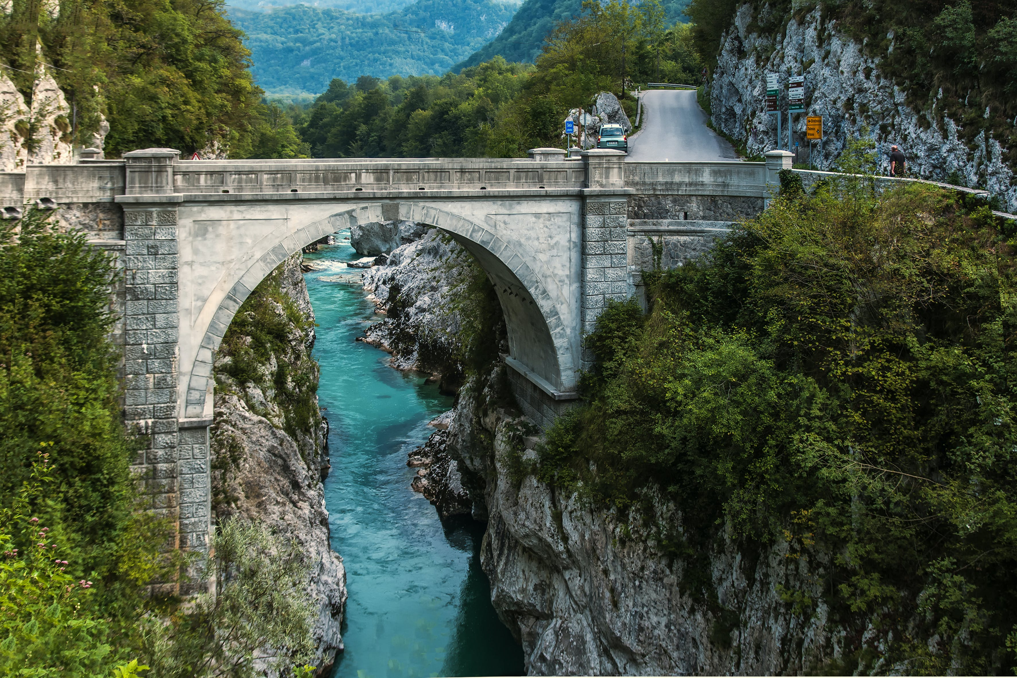 Concrete Bridge over Clear Blue River Beside Mountain