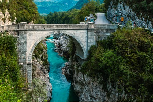 Concrete Bridge over Clear Blue River Beside Mountain
