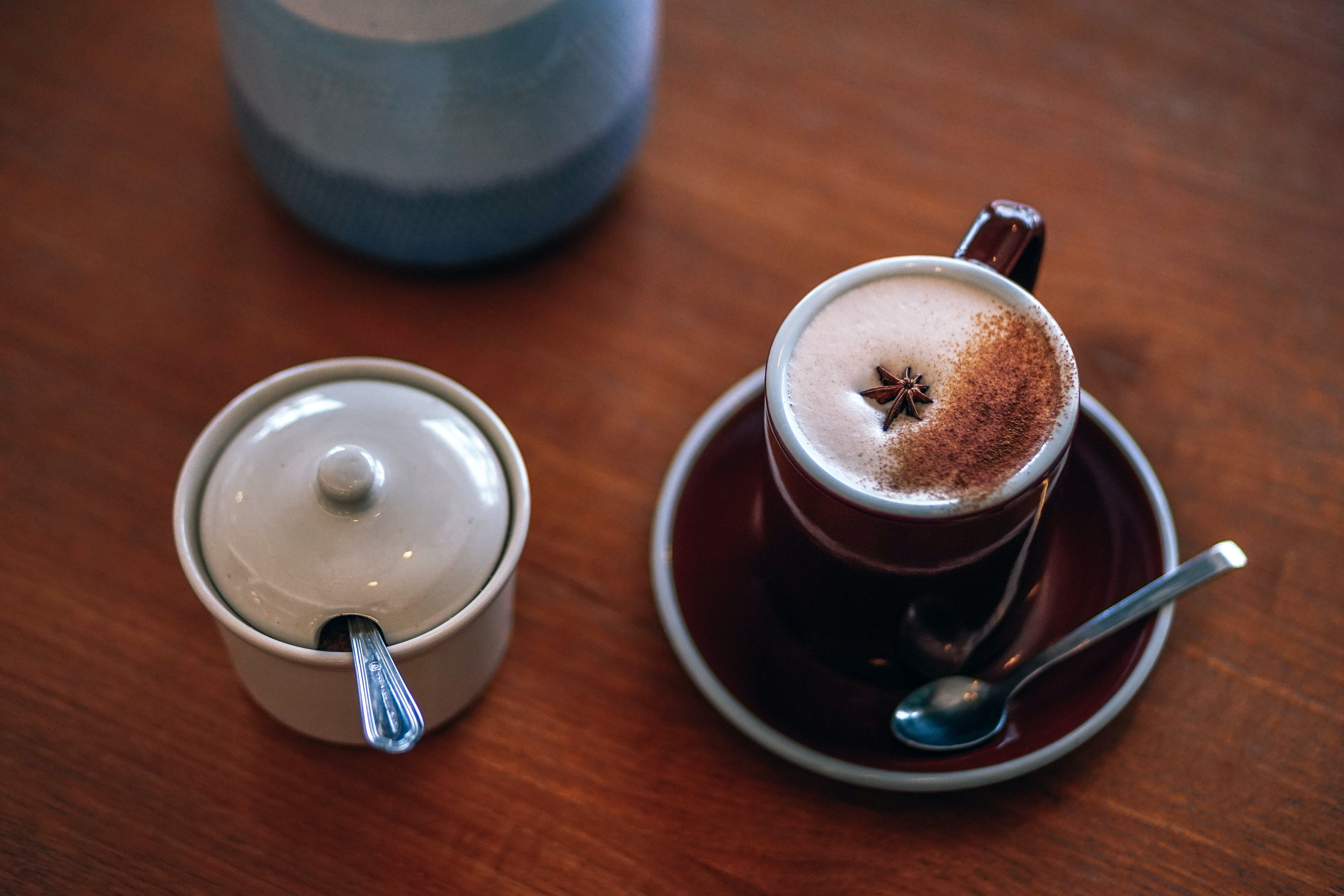 Mug of Latte Beside White Container