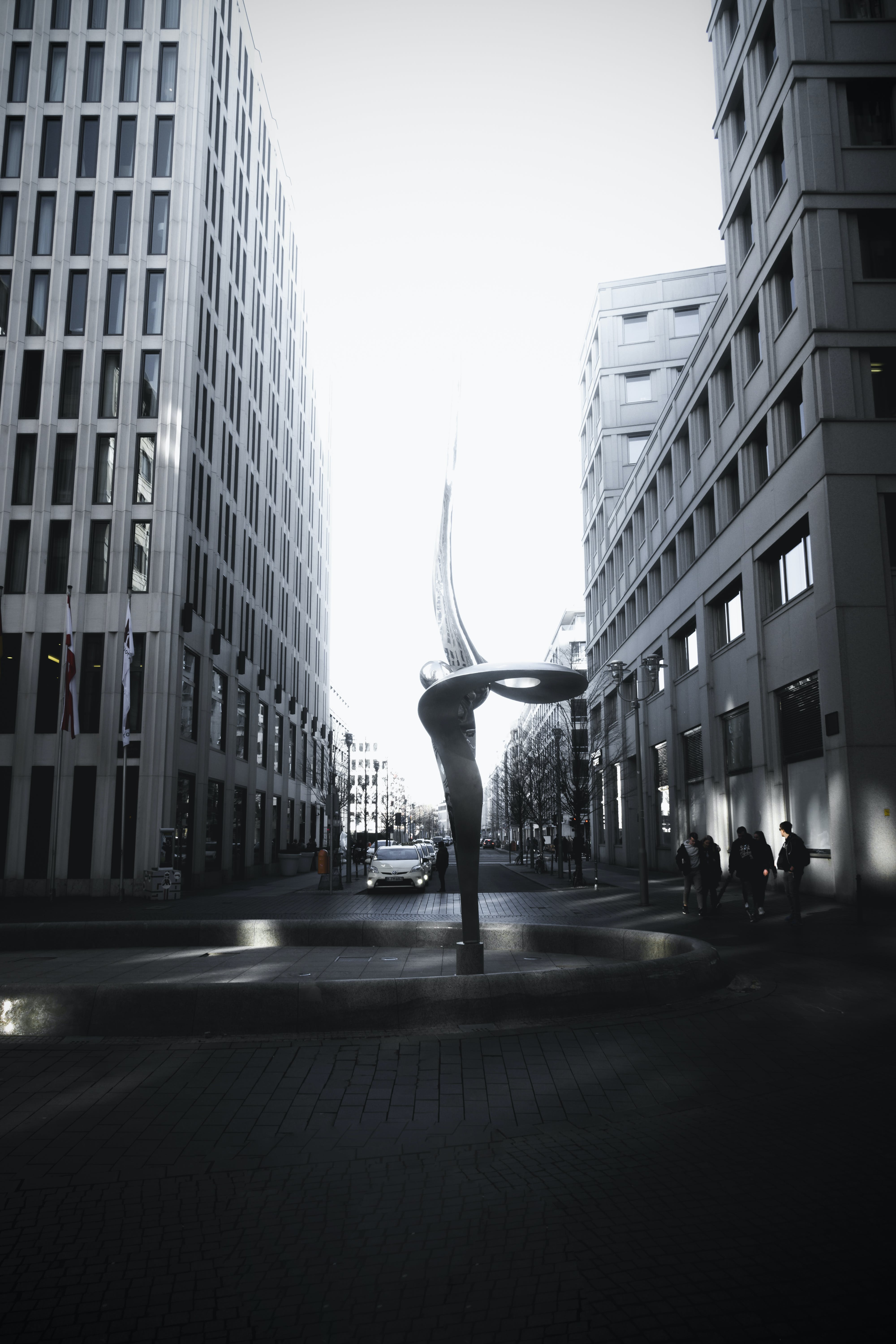 Spiral Shaped Fountain Statue Between Two High-rise Buildings