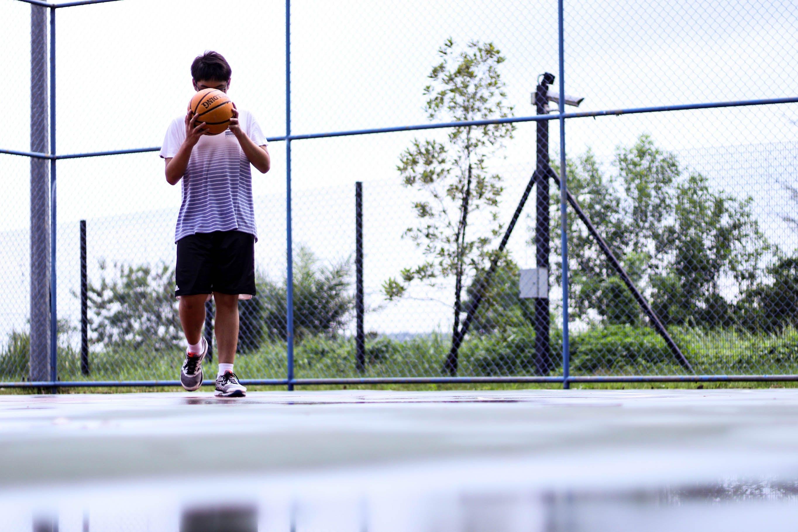 Man Holding Orange Basketball