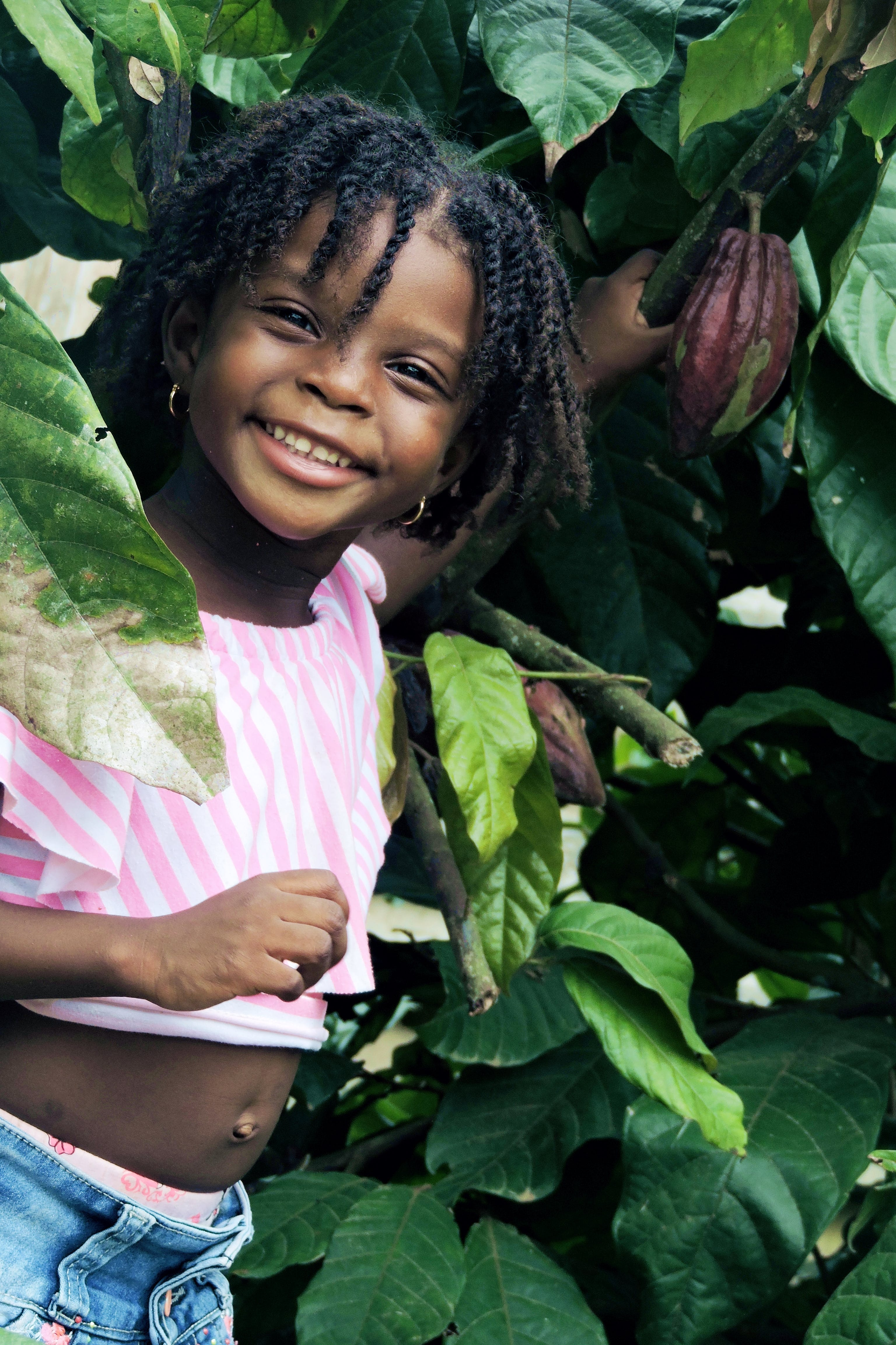 Girl Smiling Under Green Cacao Tree