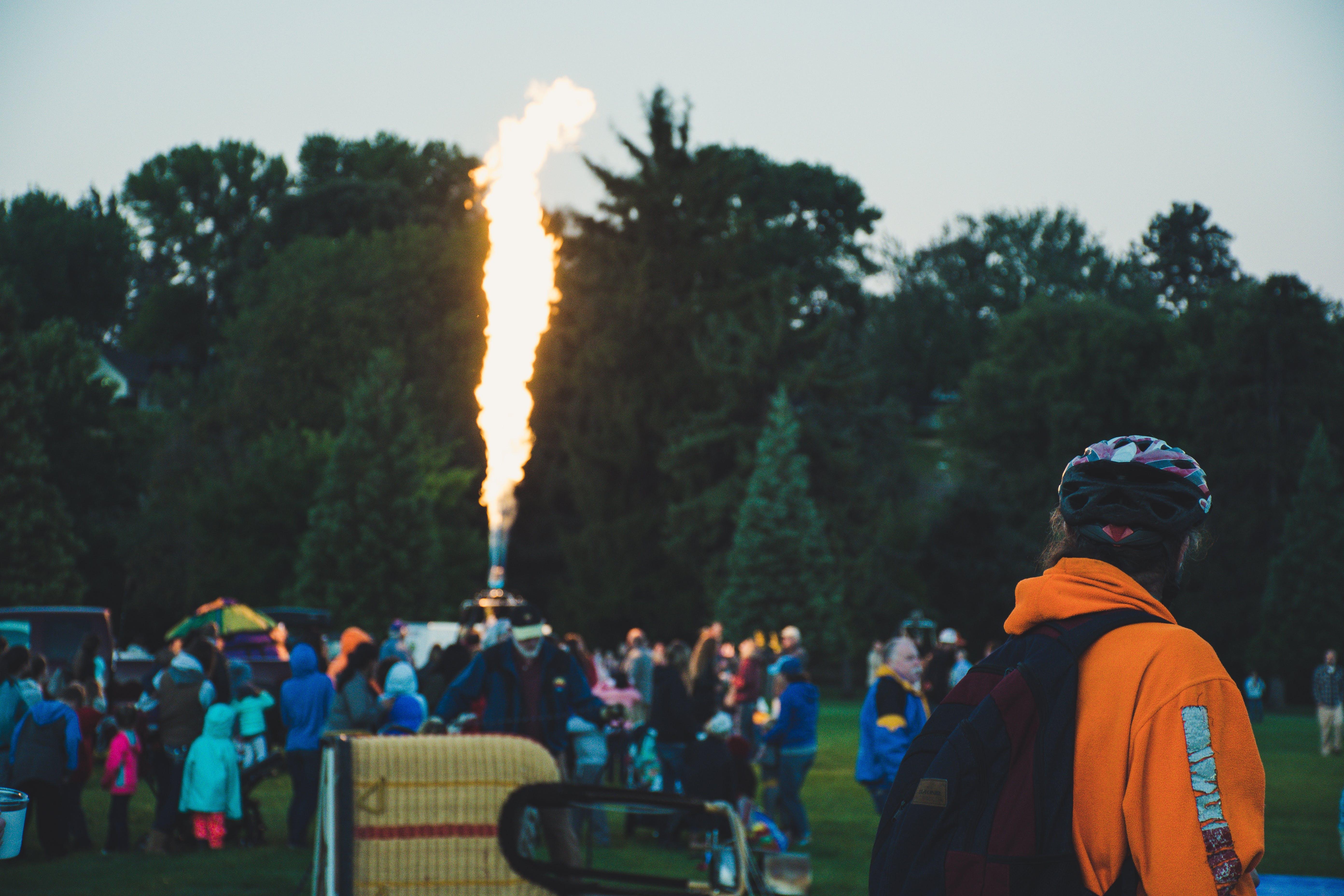 People Gathered Around Machine That Emits Flame