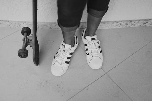 Grayscale Photography Of Person Wearing Adidas Shoes