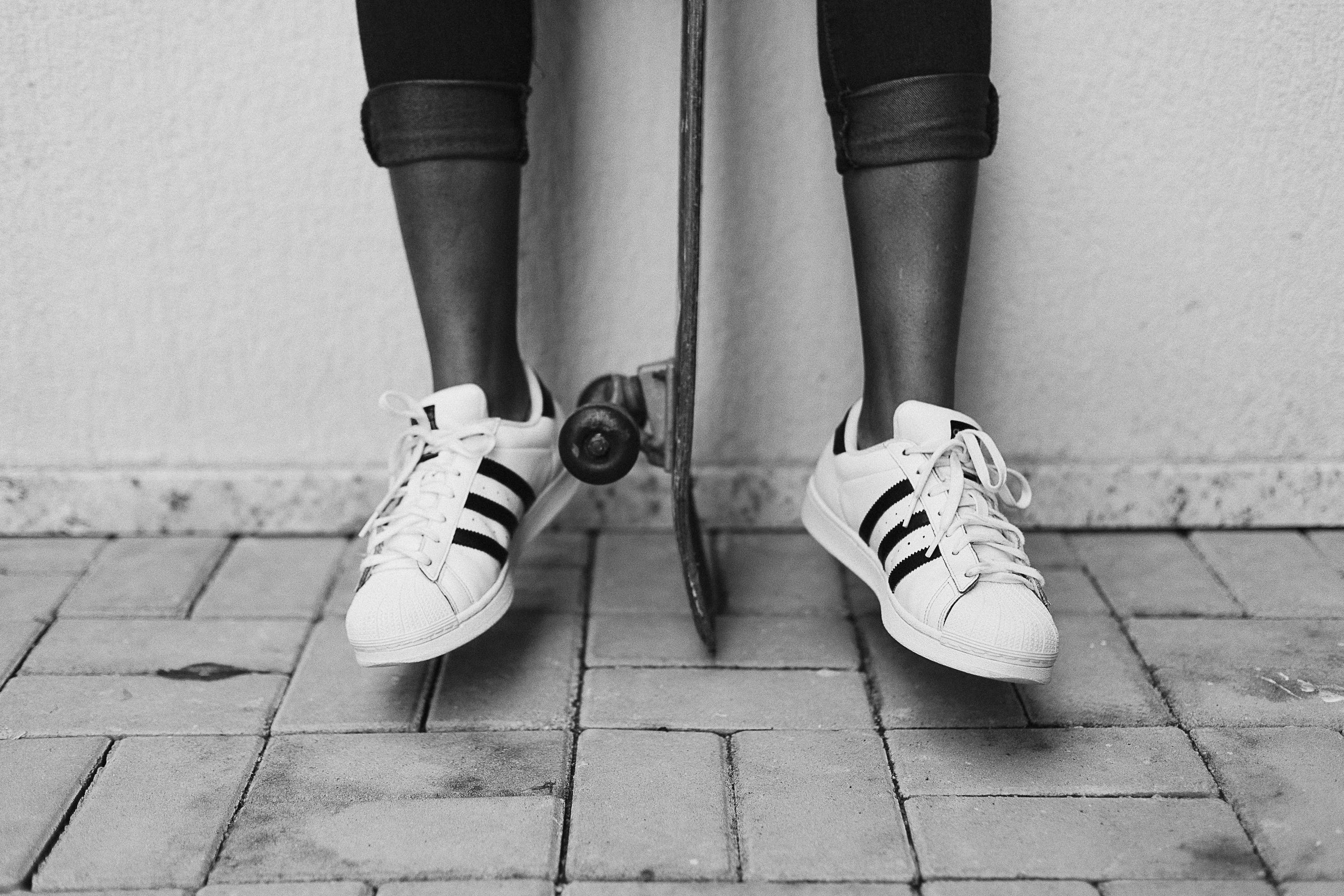 Grayscale Photo Of Shoes And Skateboard