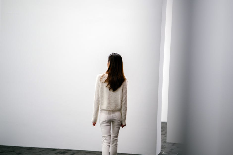 Woman Facing White Wall