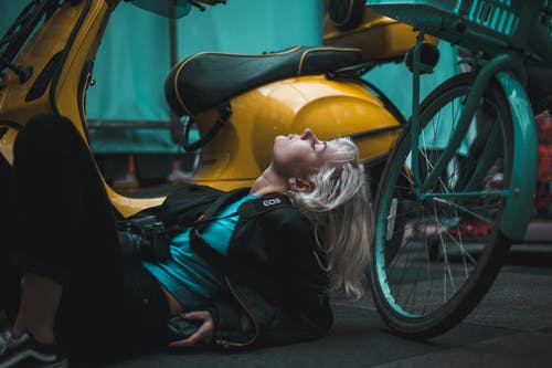 Photography of Woman Laying on Ground Near Scooter