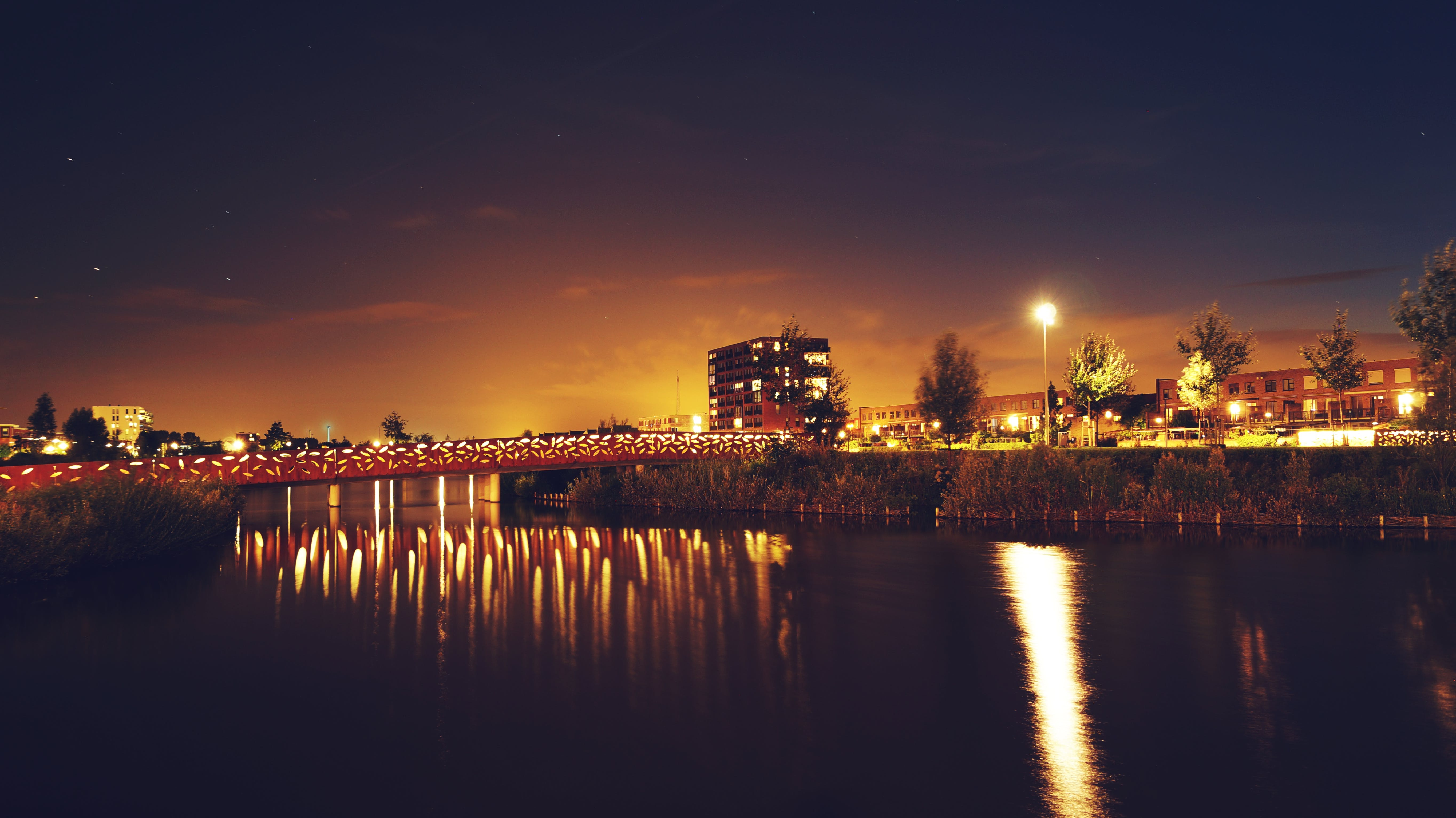 Bridge over Water Across Building during Nighttime
