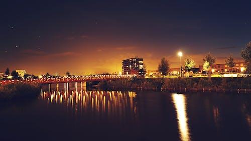 ağaçlar, akşam, aydınlatılmış, binalar içeren Ücretsiz stok fotoğraf