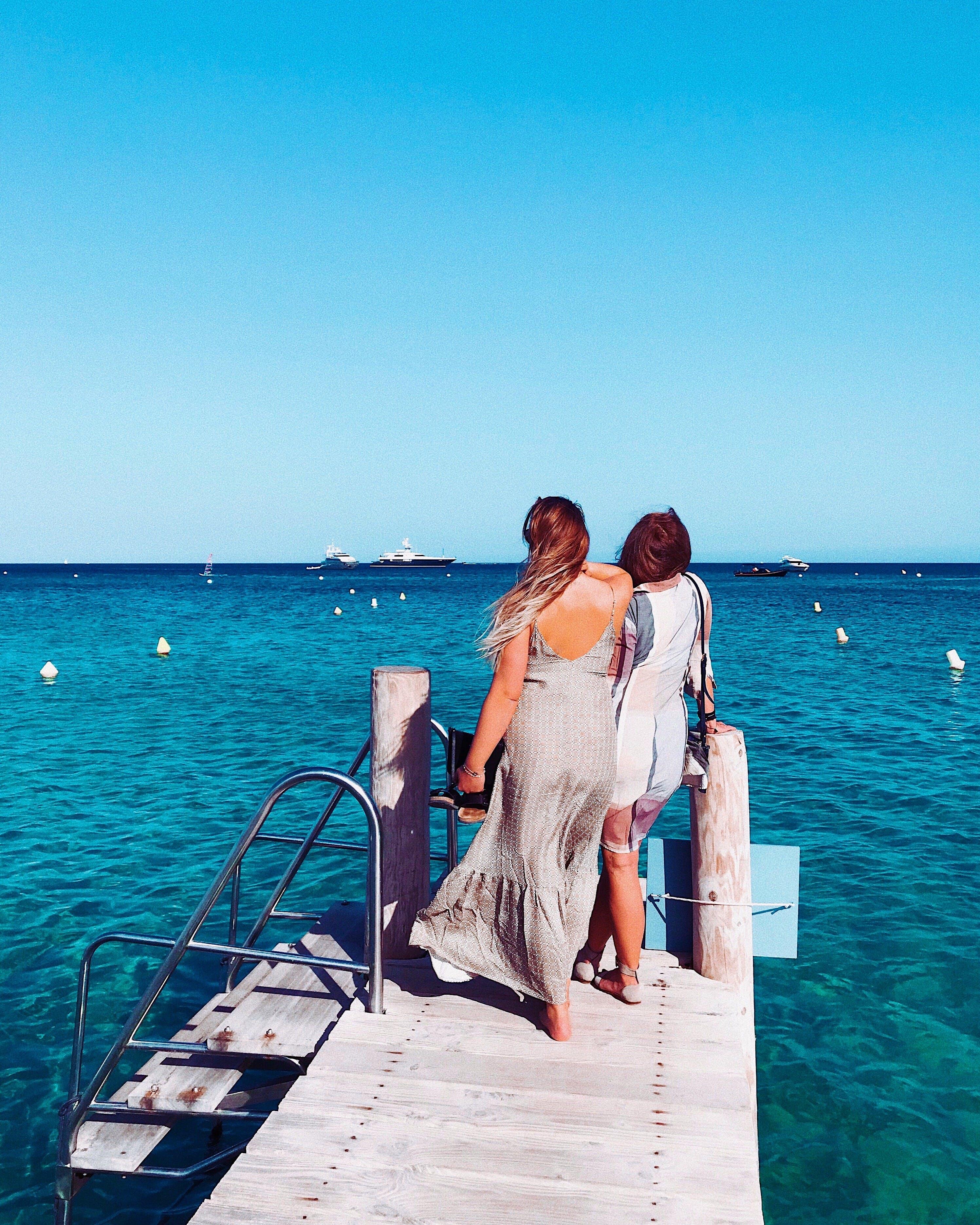 Two Women Standing On Wooden Dock