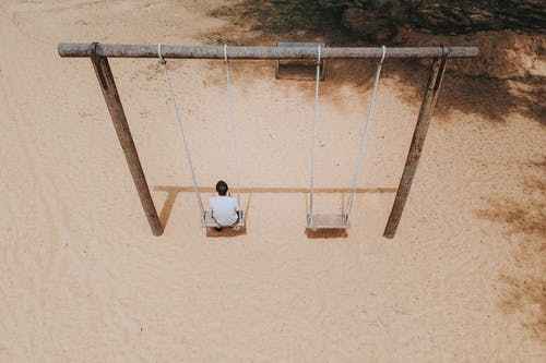 Man Sitting on Swing ]