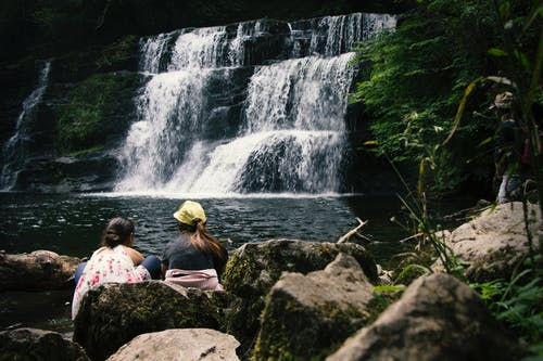 Two Women Sitting on Rock Near Waterfalls