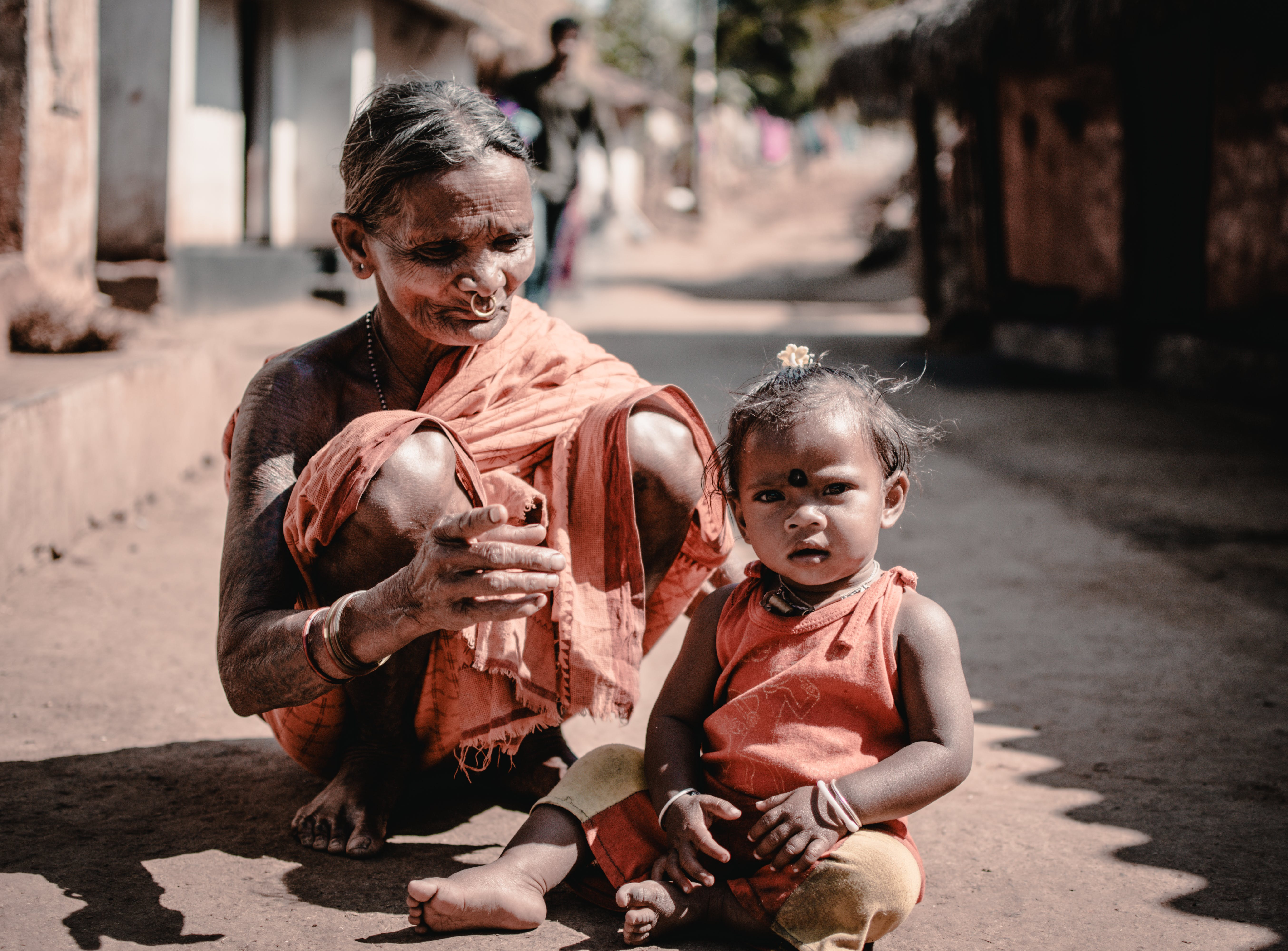 Woman and a Child Sitting on Concrete Road