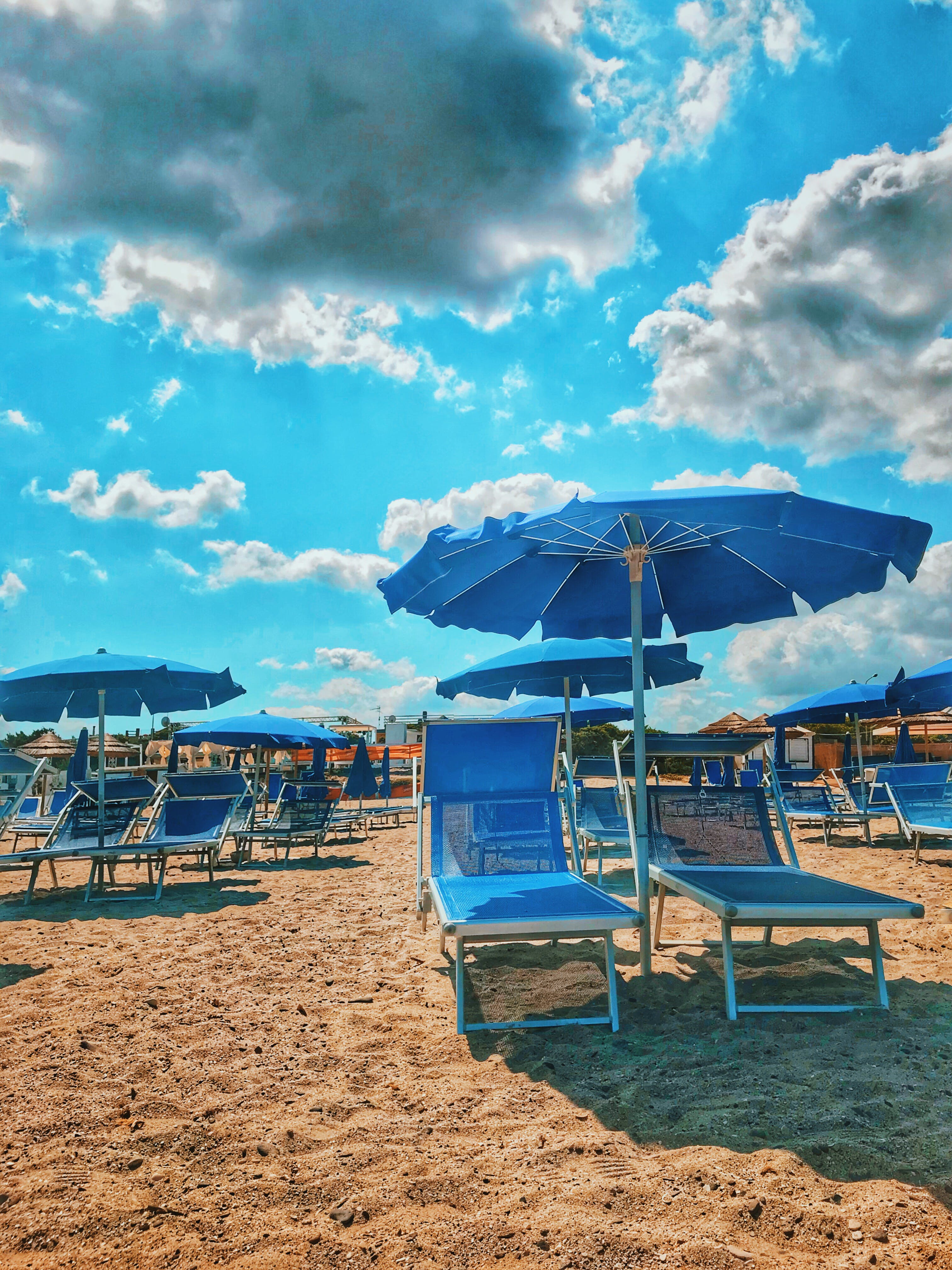 Blue Parasols And Sun Loungers On Sand