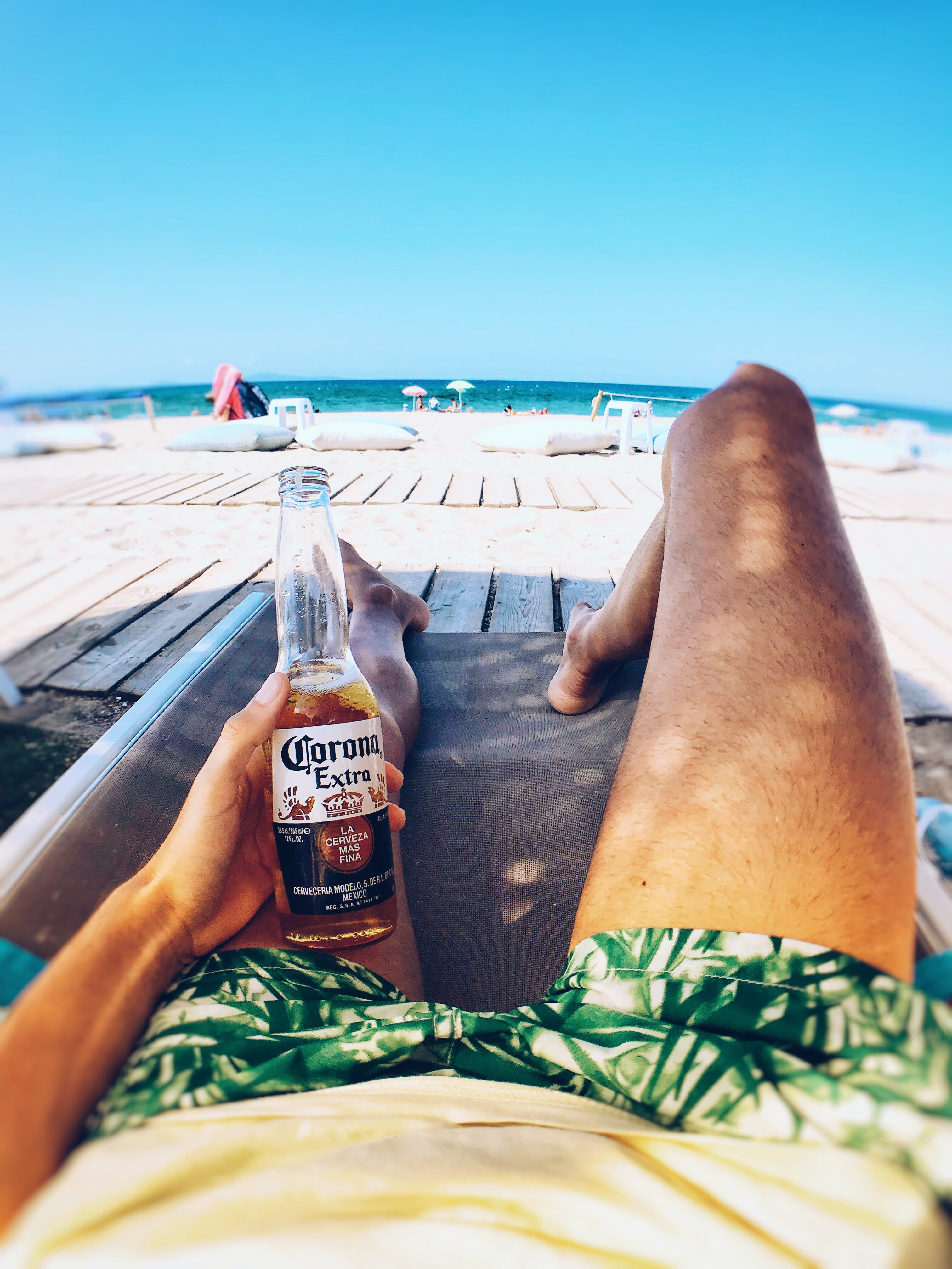 Person Laying On Lounge Chair Holding Corona Bottle