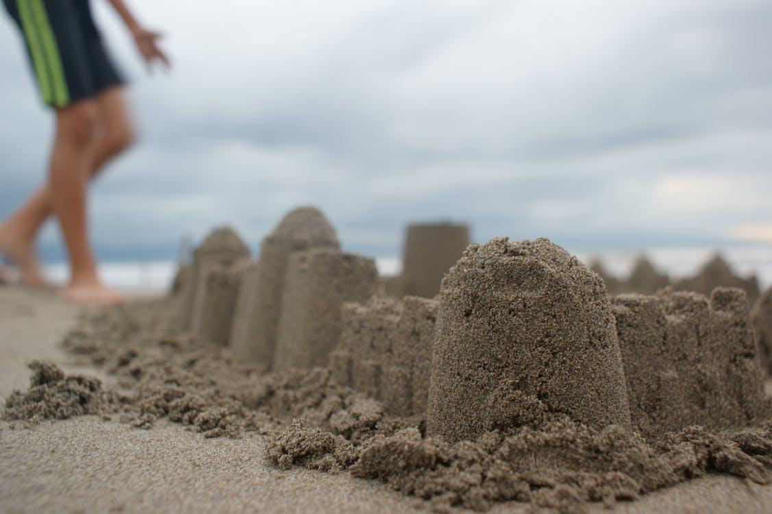 Person Standing Near Sand Castle
