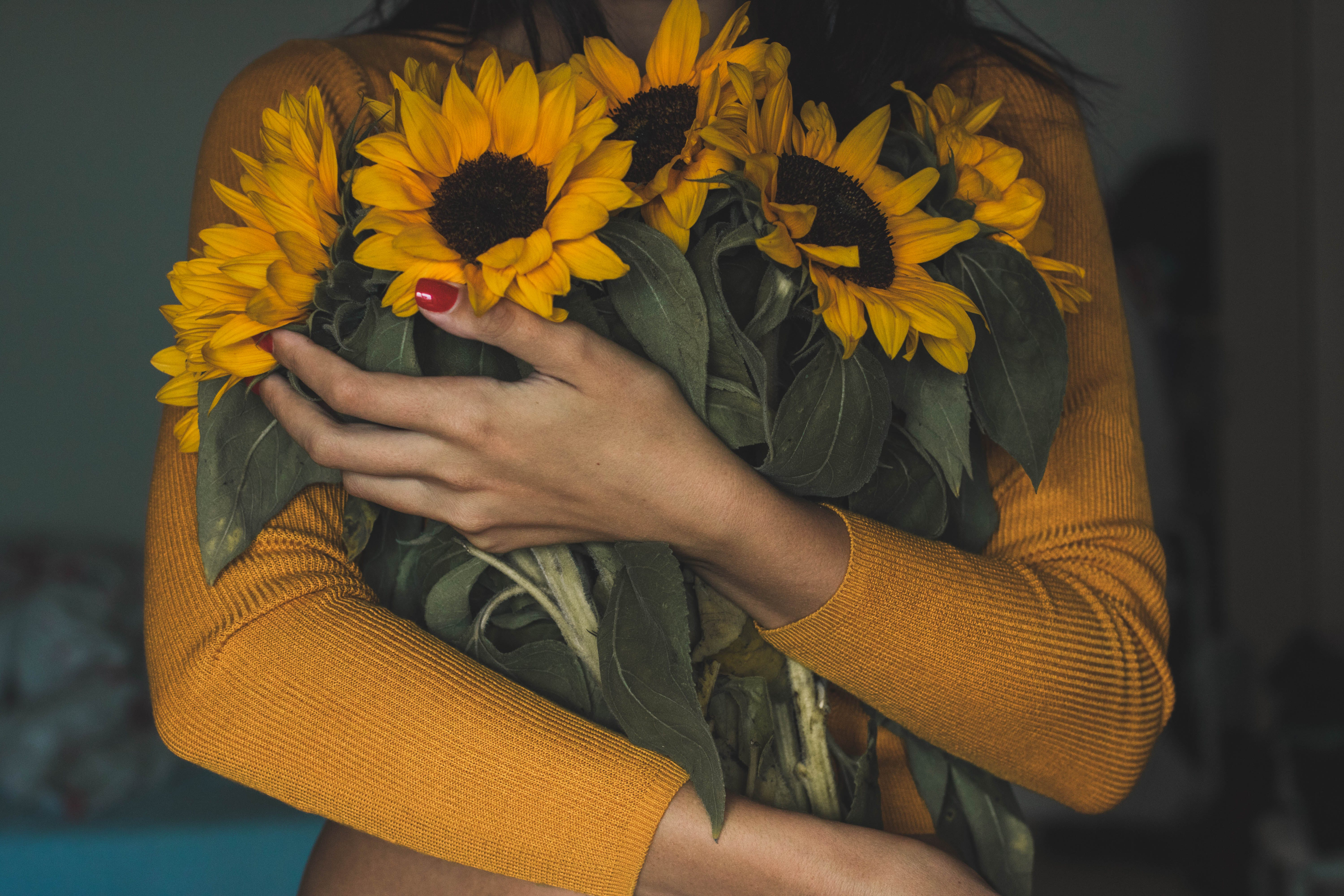 Woman Carrying Bunch Of Sunflowers
