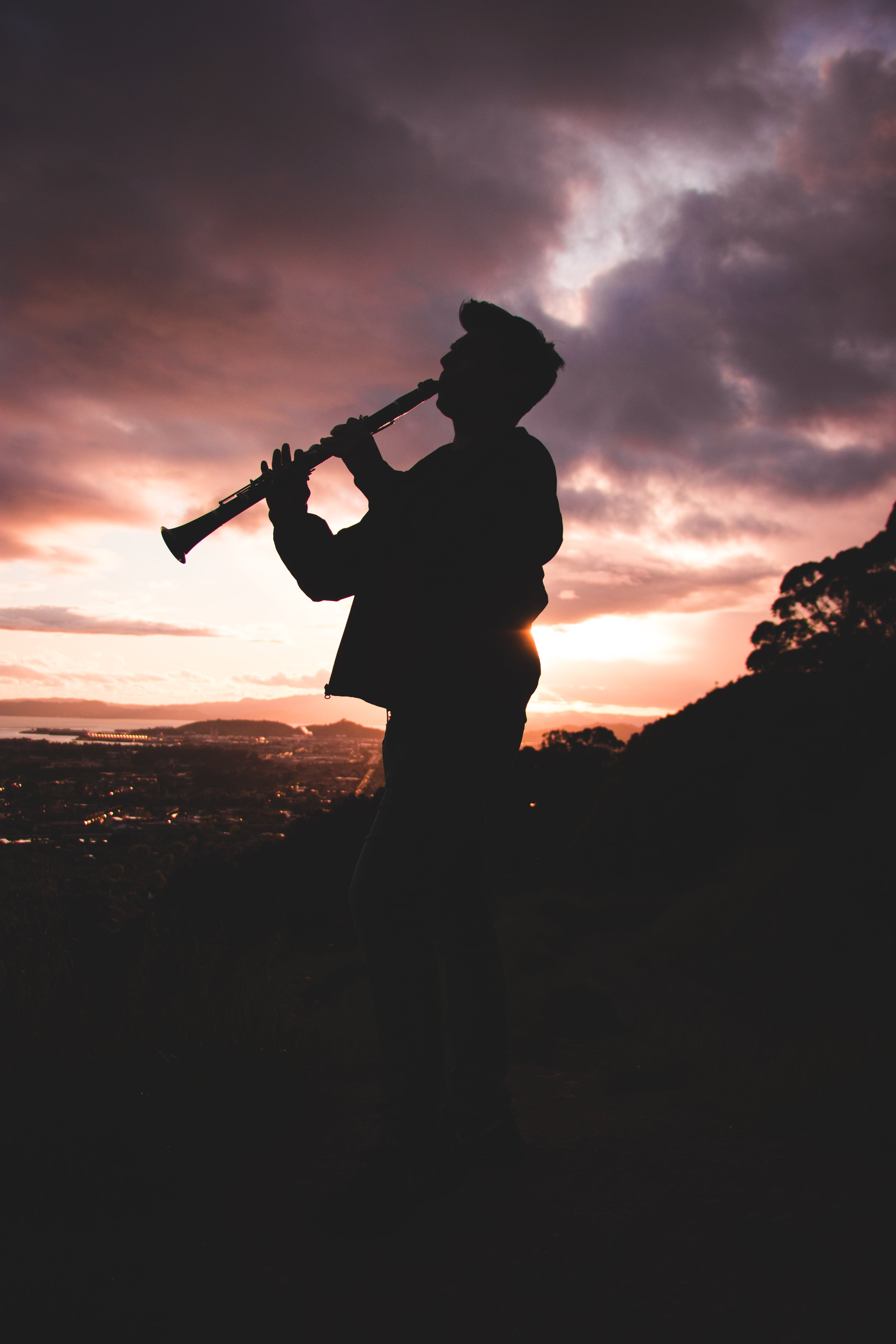 Silhouette Photo Of Person Playing Clarinet