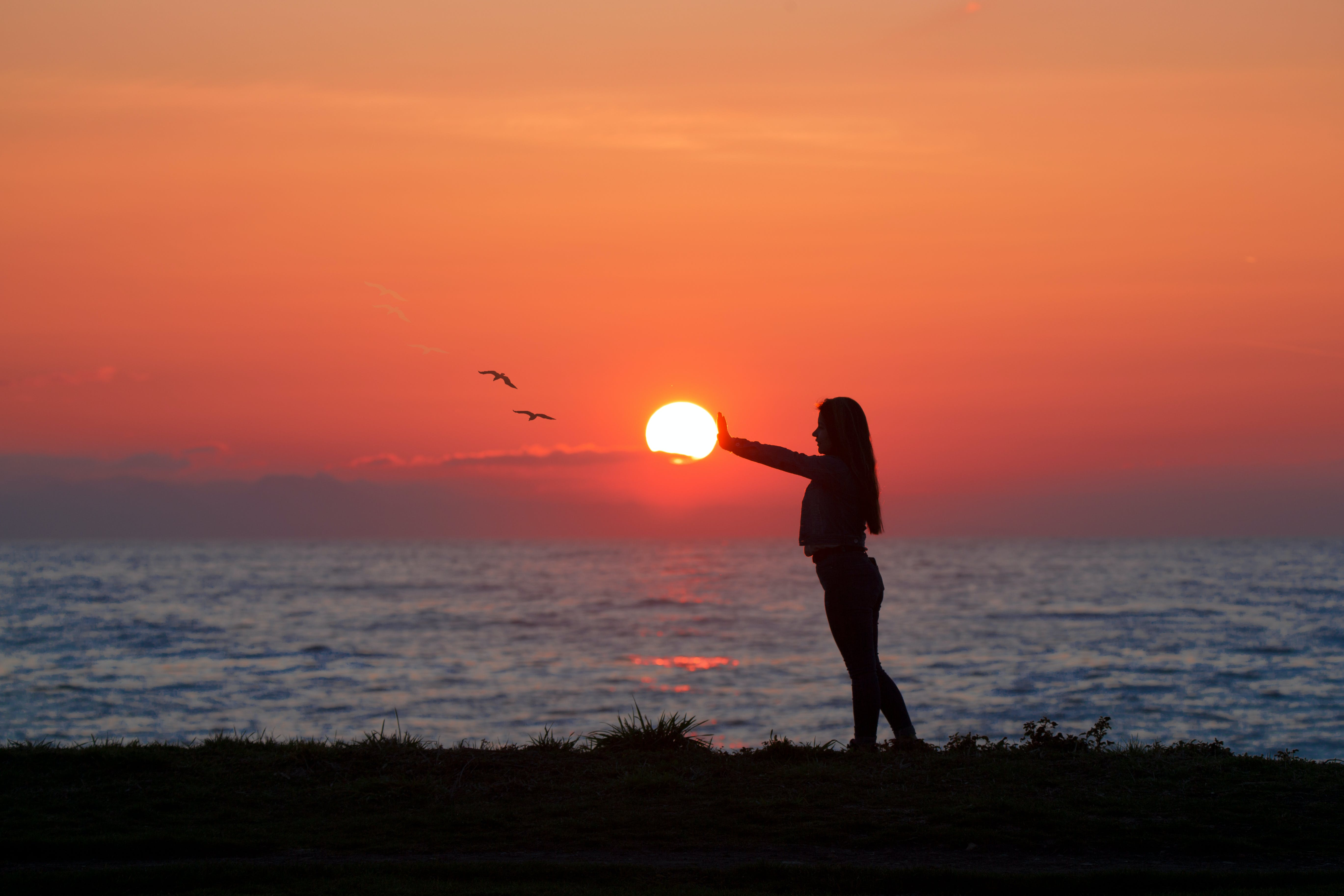 Photo of Woman Standing On Seashore During Dawn