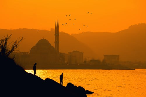 Silhouette of Two People Near Sea in Distant of  Ortakoy Mosque, Istanbul Turkey