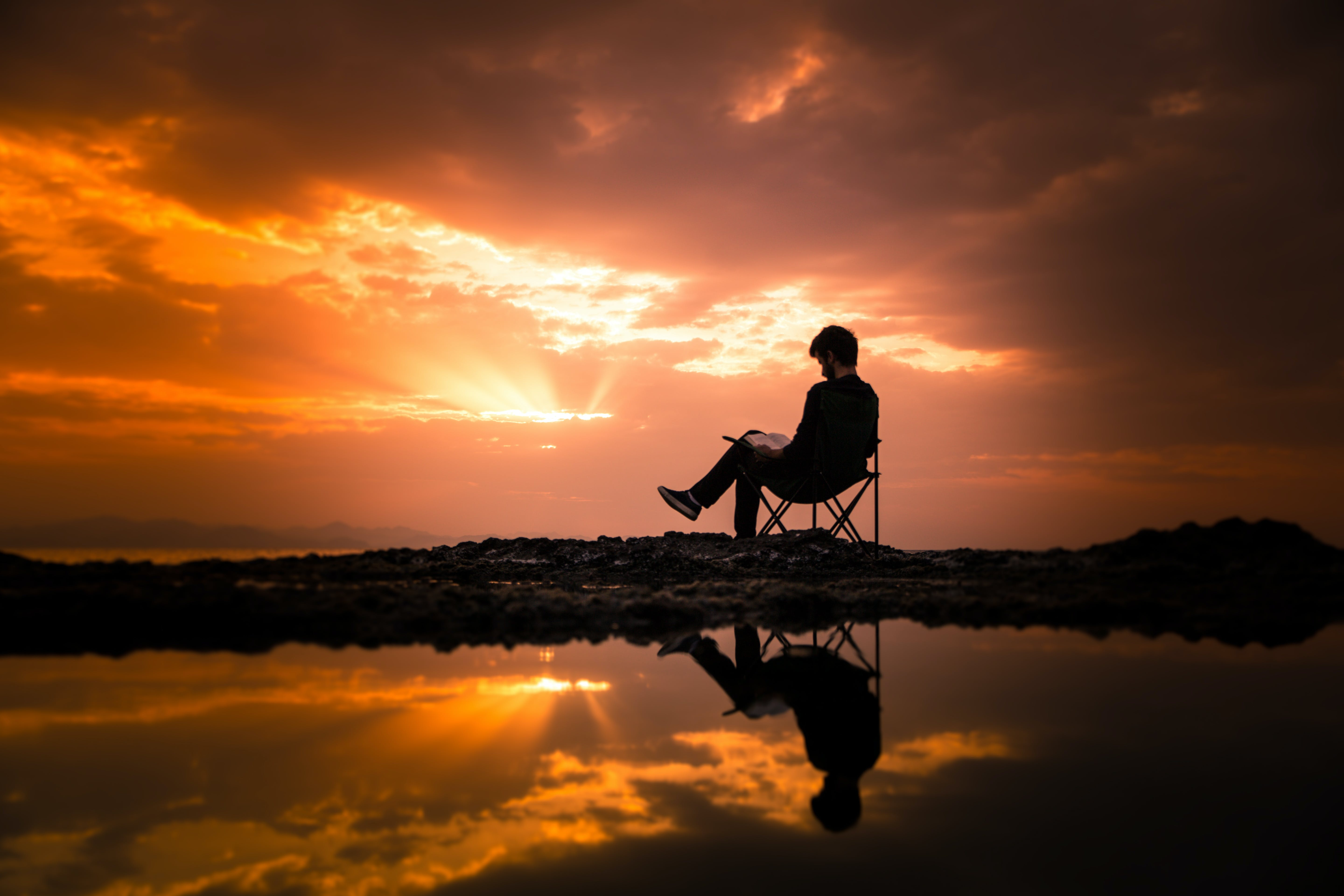 Photo of Man Sitting on Camping Chair During Dawn