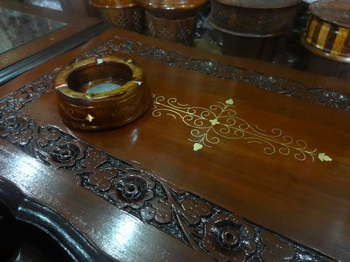 Free stock photo of ashtray, carved wood, wooden table