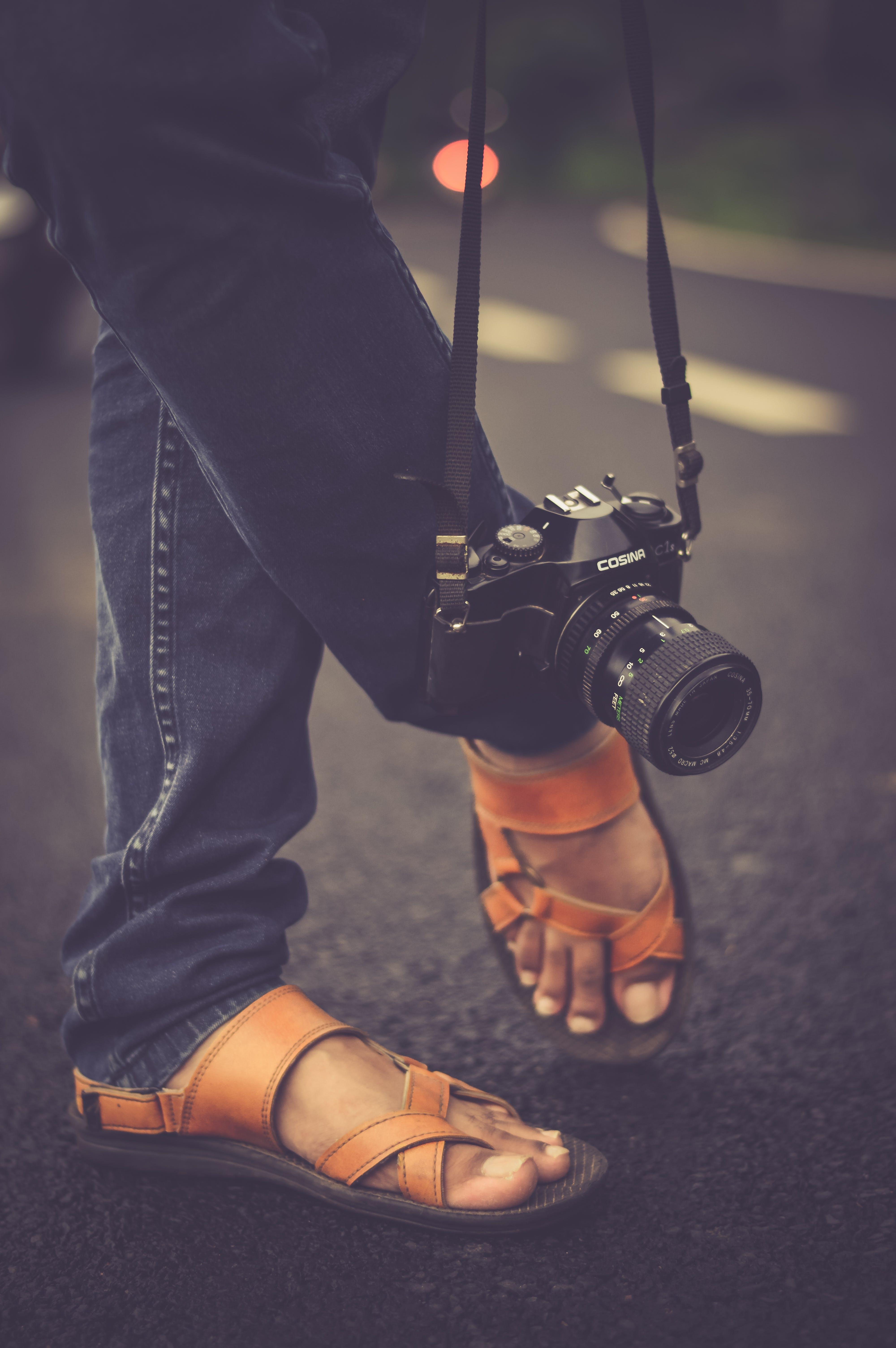 Black Cosina Slr Camera Hanging Beside Foot during Daytime