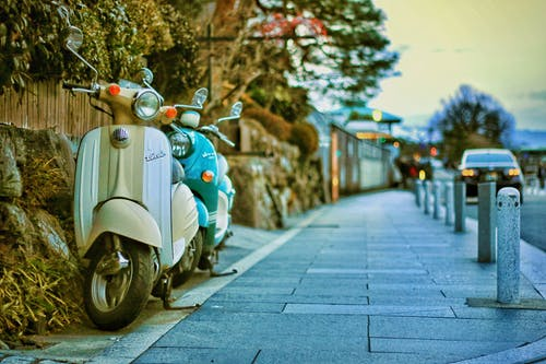 Two Beige and Teal Motor Scooters on Street