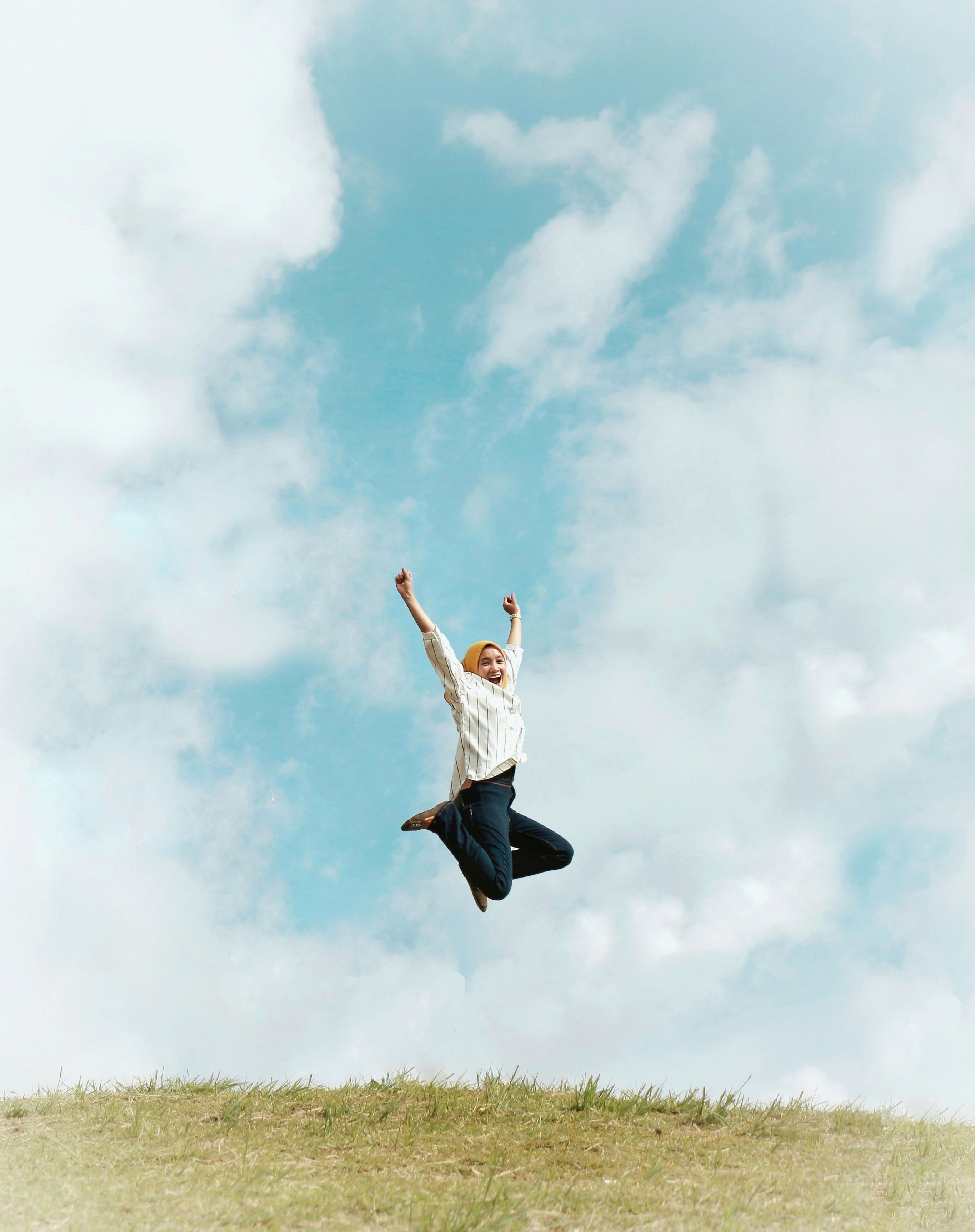 Person Jumping On Air With Clouds Background