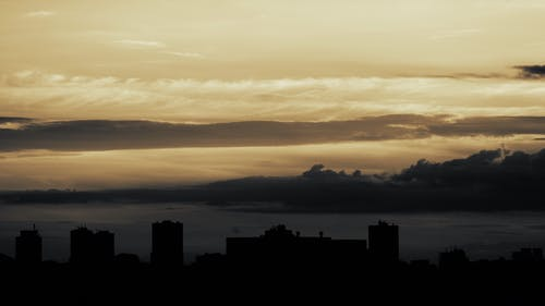 Silhouette of Buildings Near Body of Water during Golden Hour
