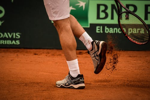 Man Wearing Black-and-white Asics Athletic Shoes Holding Racket